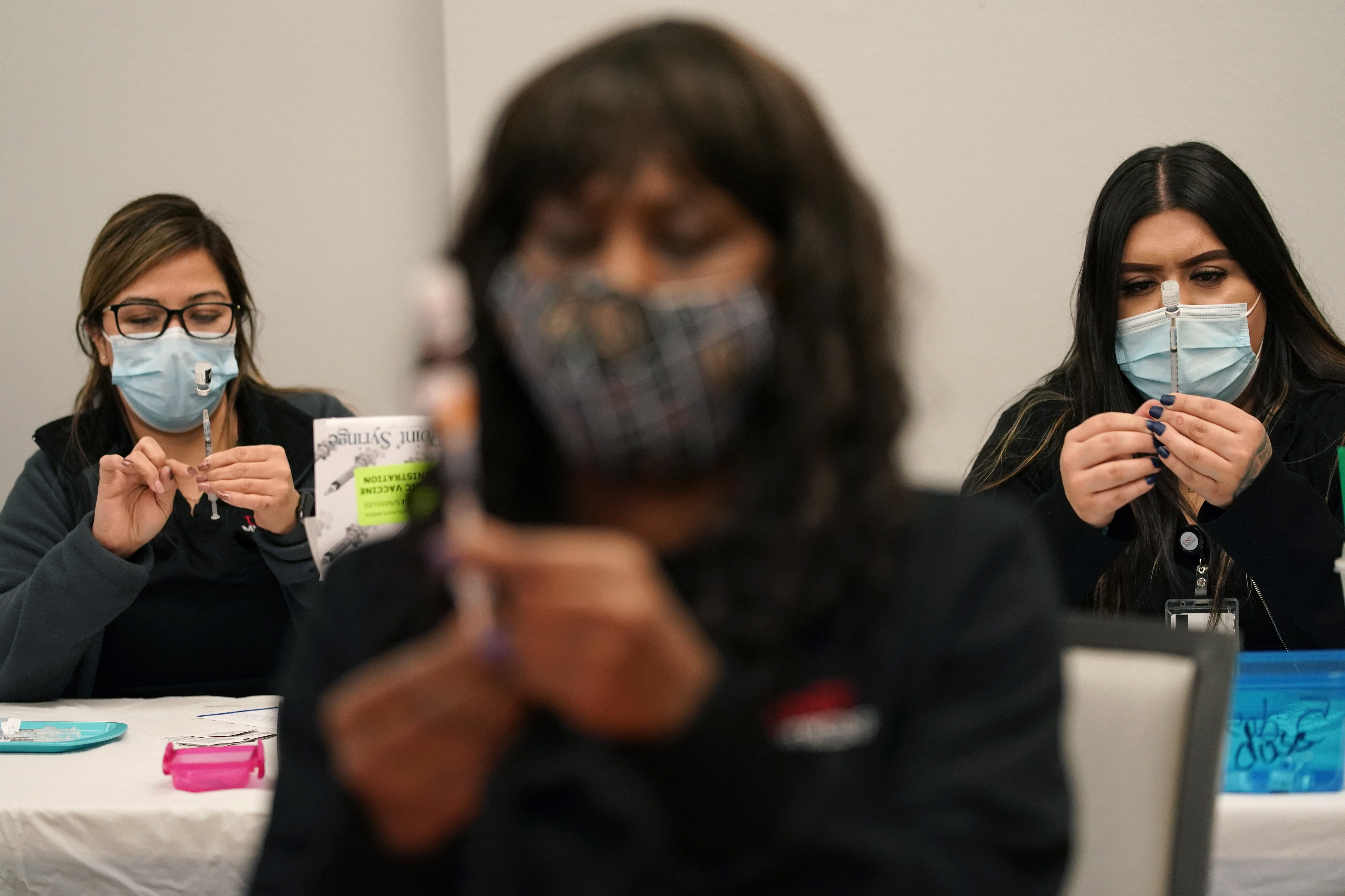 In this Jan. 22, 2021, file photo, certified medical assistants Martha Sida, from left, Tina Killebrew and Cynthia Bernal prepare doses of the Pfizer-BioNTech COVID-19 vaccine at a vaccination center at the University of Nevada, Las Vegas, in Las Vegas.