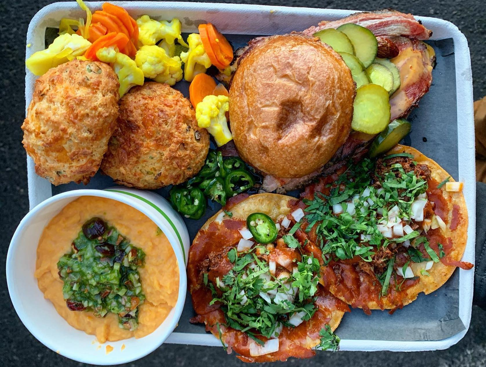 A half sheet pan serving tray from Animales Barbecue piled high with offerings. A cheesy bowl of soup, bun covered meat sandwich, two cheesy biscuits, birria tacos, and pickles