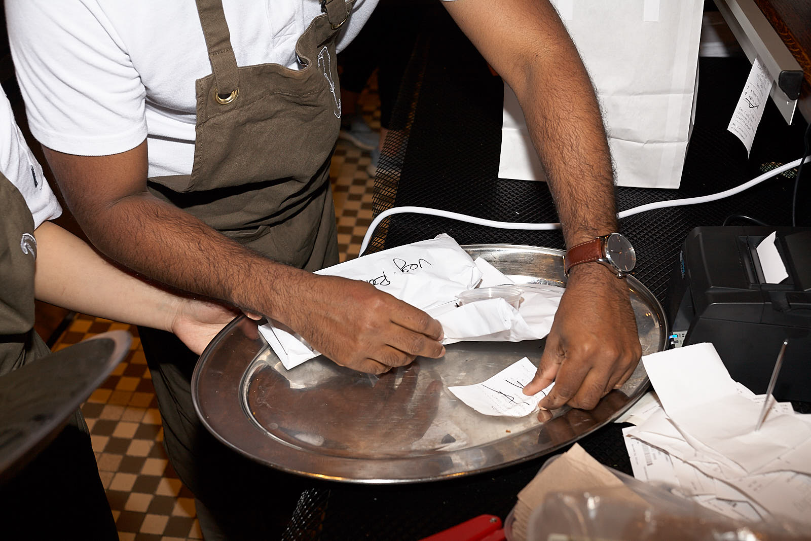 A waiter sorts through checks at Darjeeling Express last November, just after the restaurant first opened for guests. It's the second incarnation of chef Asma Khan's Soho Indian restaurant which has won critical accliam