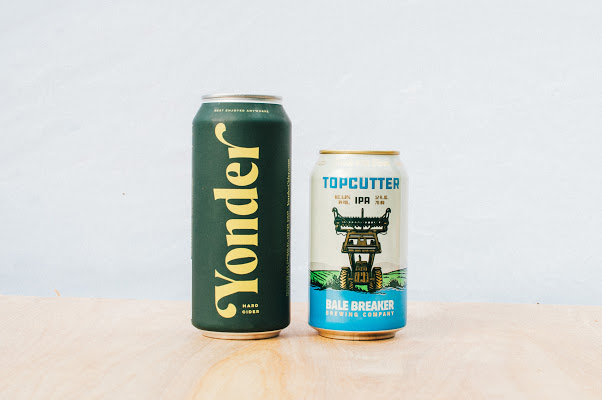 A green can of Yonder Cider next to a can of Bale Breaker's Topcutter IPA