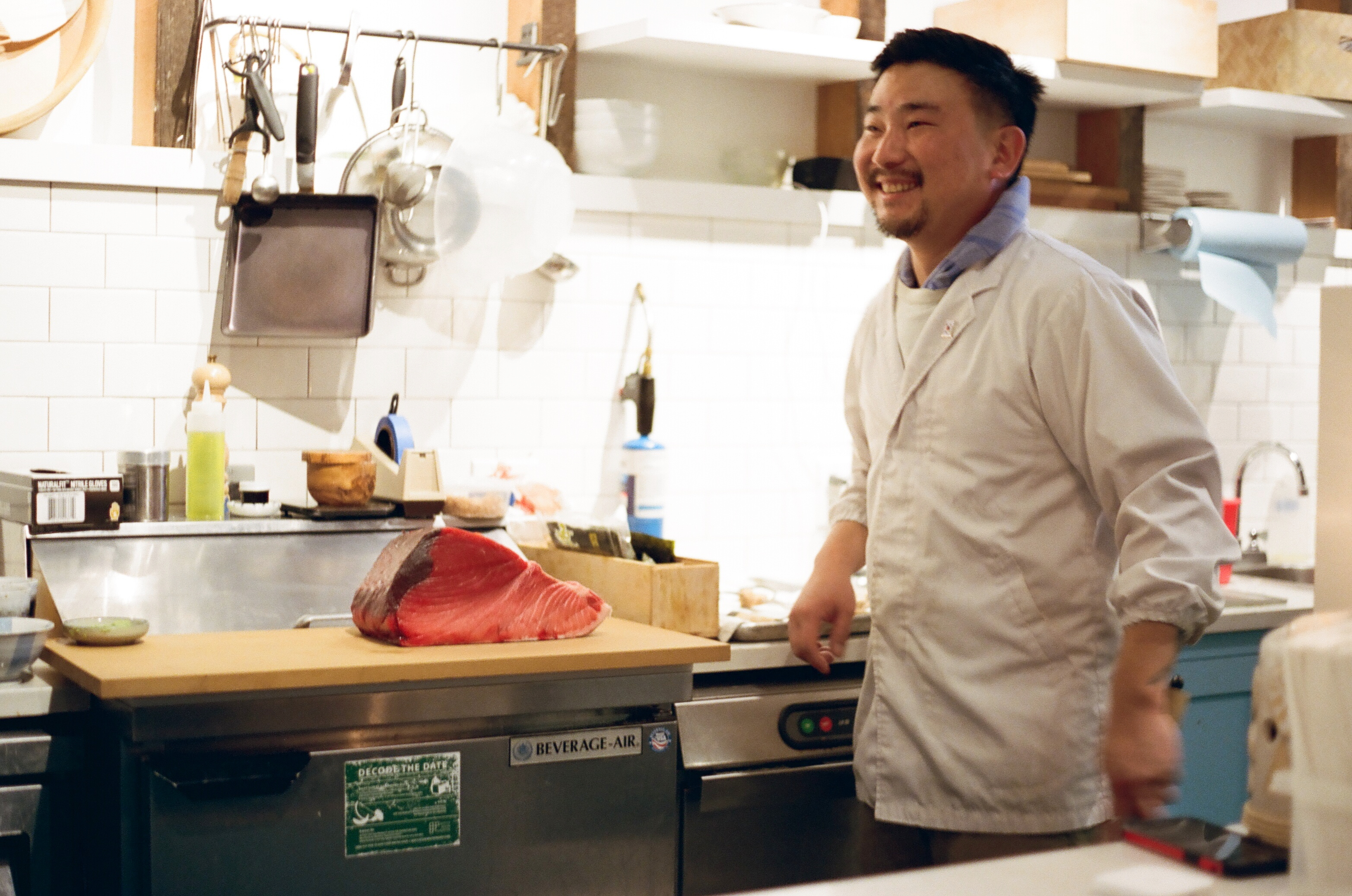 Chef Sun Hong at his Capitol Hill lunch counter By Tae, next to a giant cut of fish.