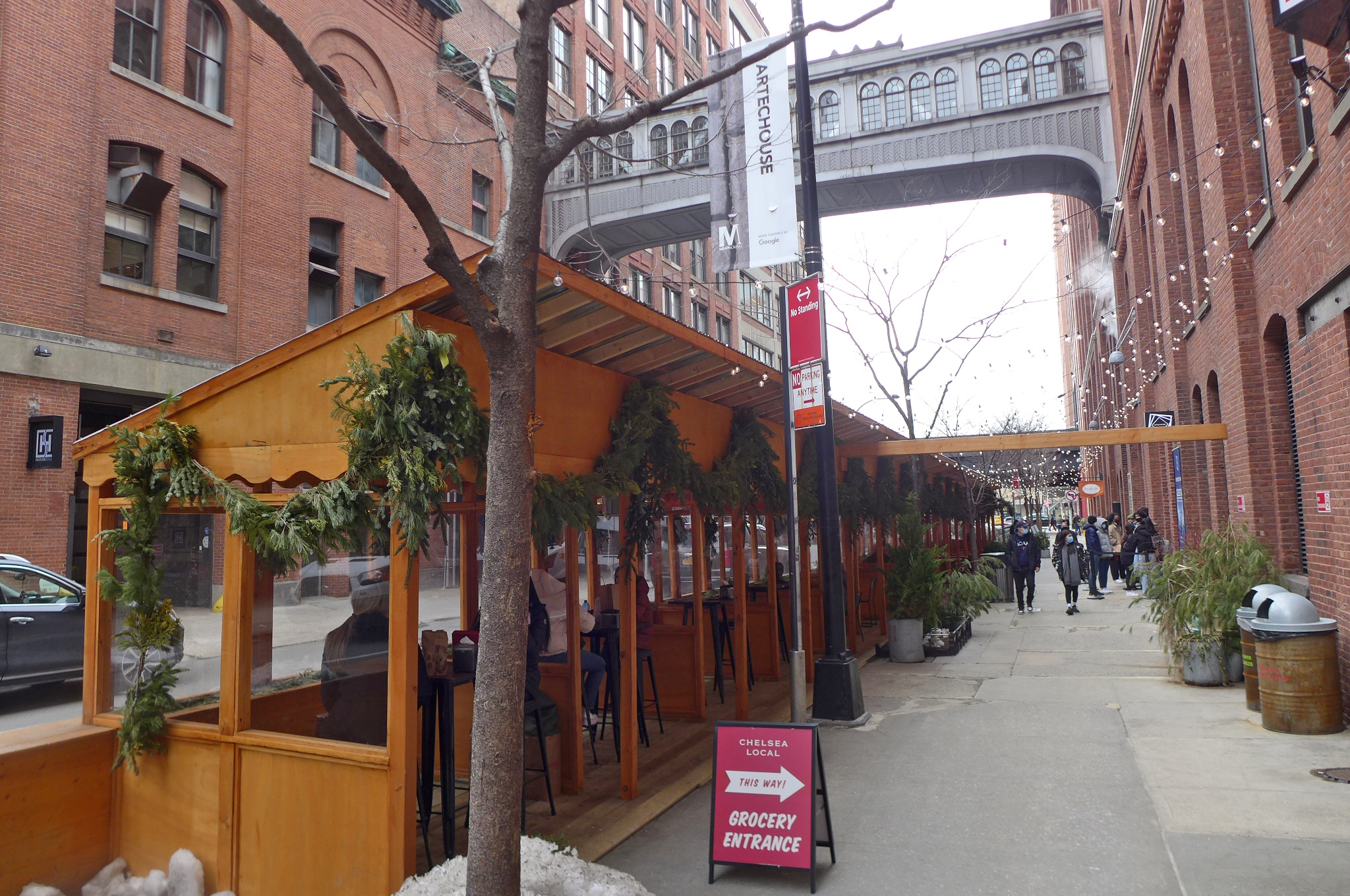Wooden outdoor dining kiosks in foreground with bridge between two ancient brick buildings up above.
