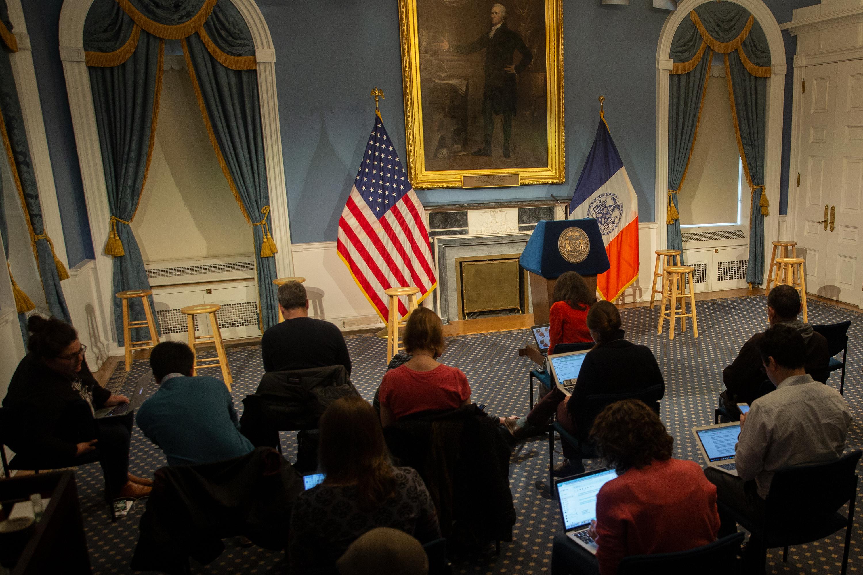Periodistas mantienen el distanciamiento social mientras se preparan para una conferencia de prensa con el alcalde Bill de Blasio, 16 de marzo, 2020.