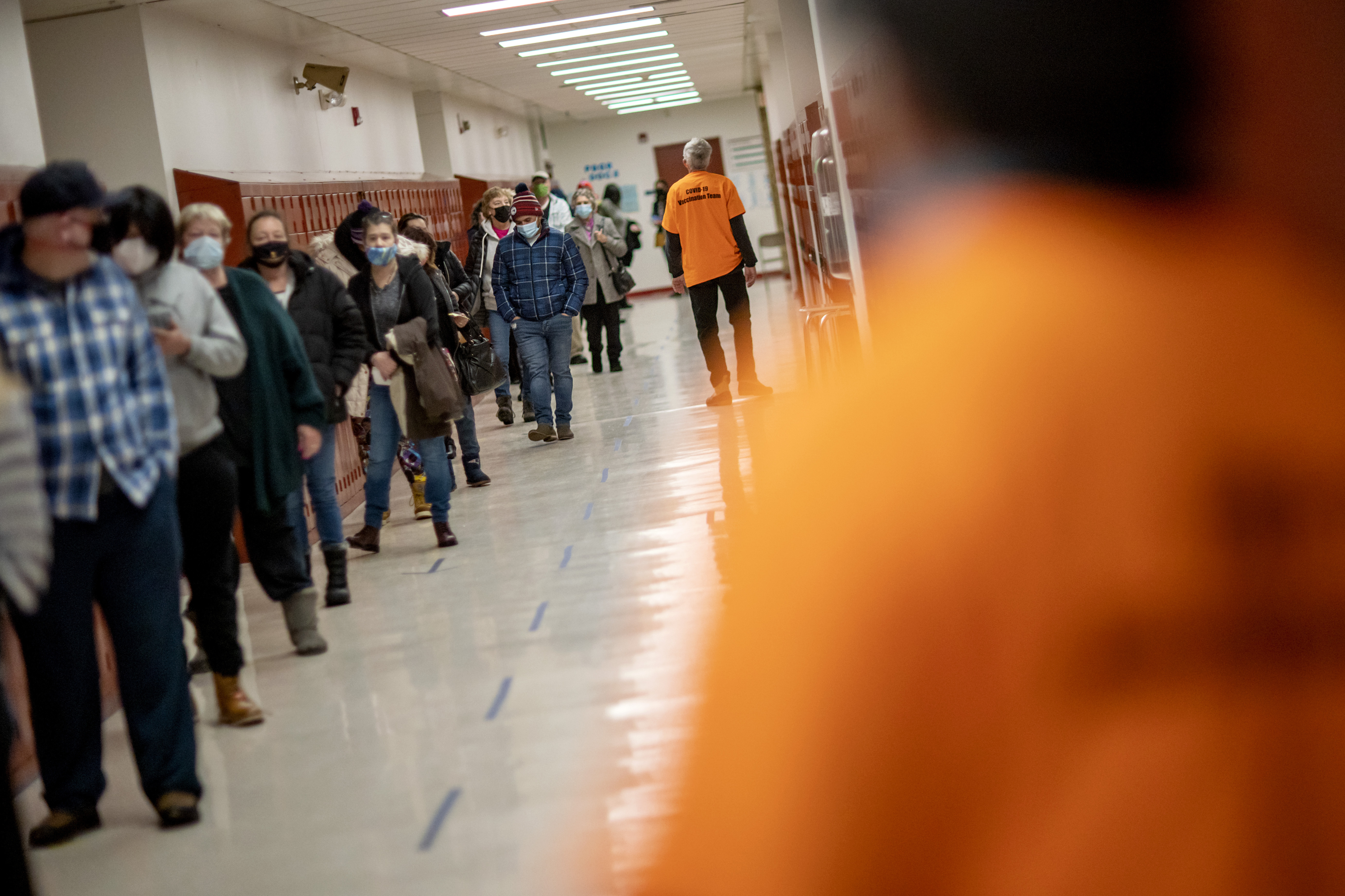 People line up for vaccines at a clinic in Central Falls, R.I., Saturday Feb. 20, 2021. Nearly a third of adults in the city have received at least one dose of vaccine, according to state data. Health officials say the city of about 20,000 has seen a marked drop in COVID-19 cases as a result.
