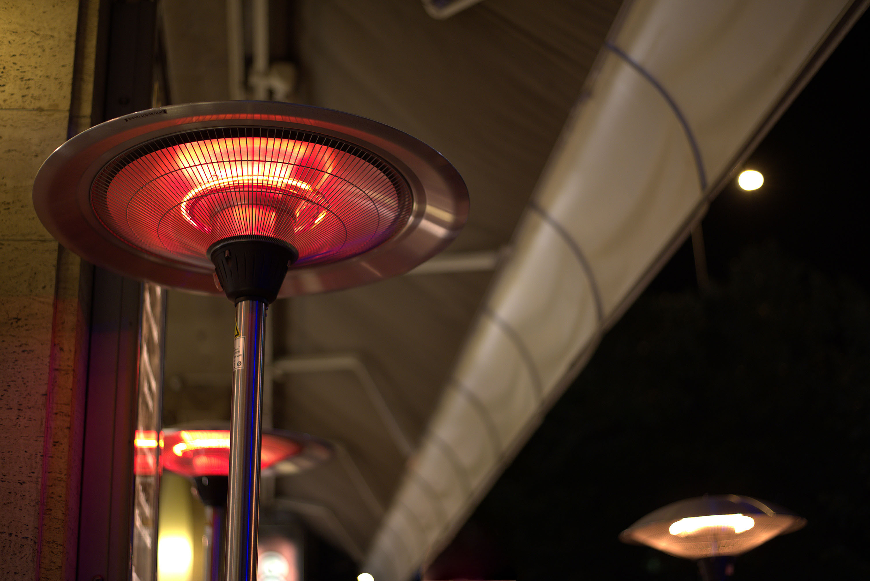 Shot from below, an electric heat lamp glows under the awning of a restaurant at night.
