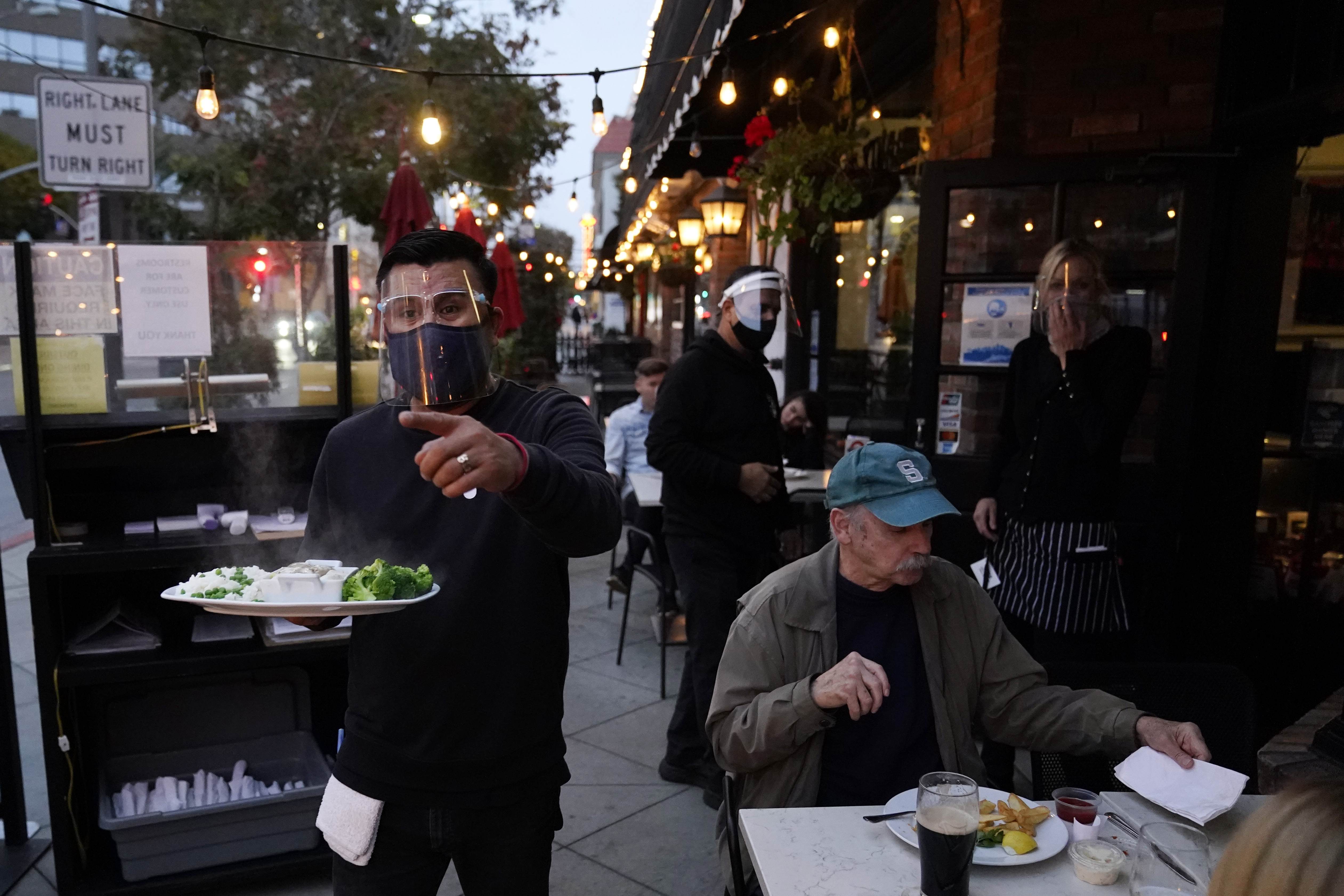 In this Nov. 19, 2020, file photo, a server carries food for a customer at Ye Olde King's Head in Santa Monica, Calif.
