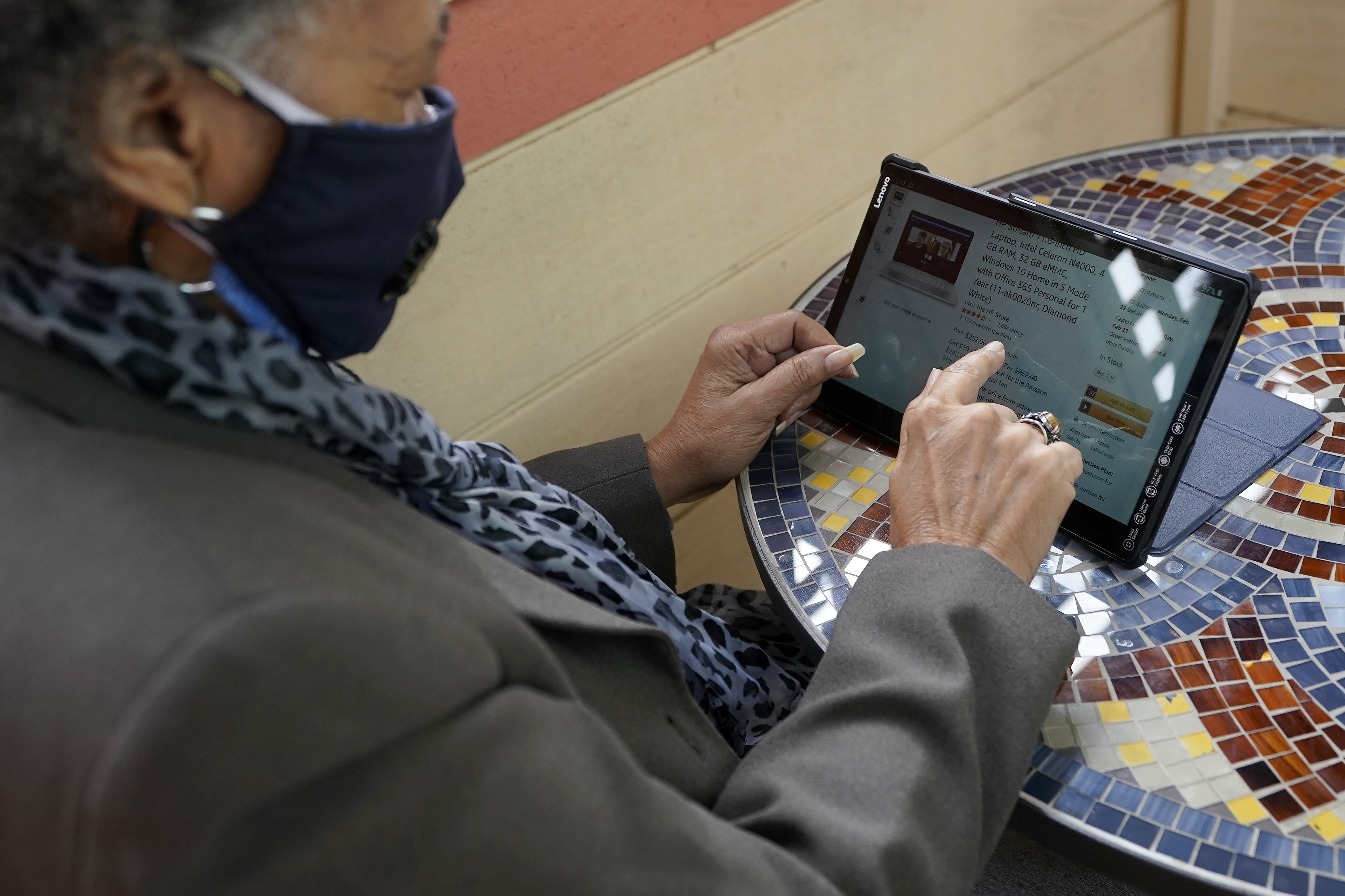 Lynnette White uses her tablet while interviewed in San Francisco, Tuesday, Feb. 16, 2021.
