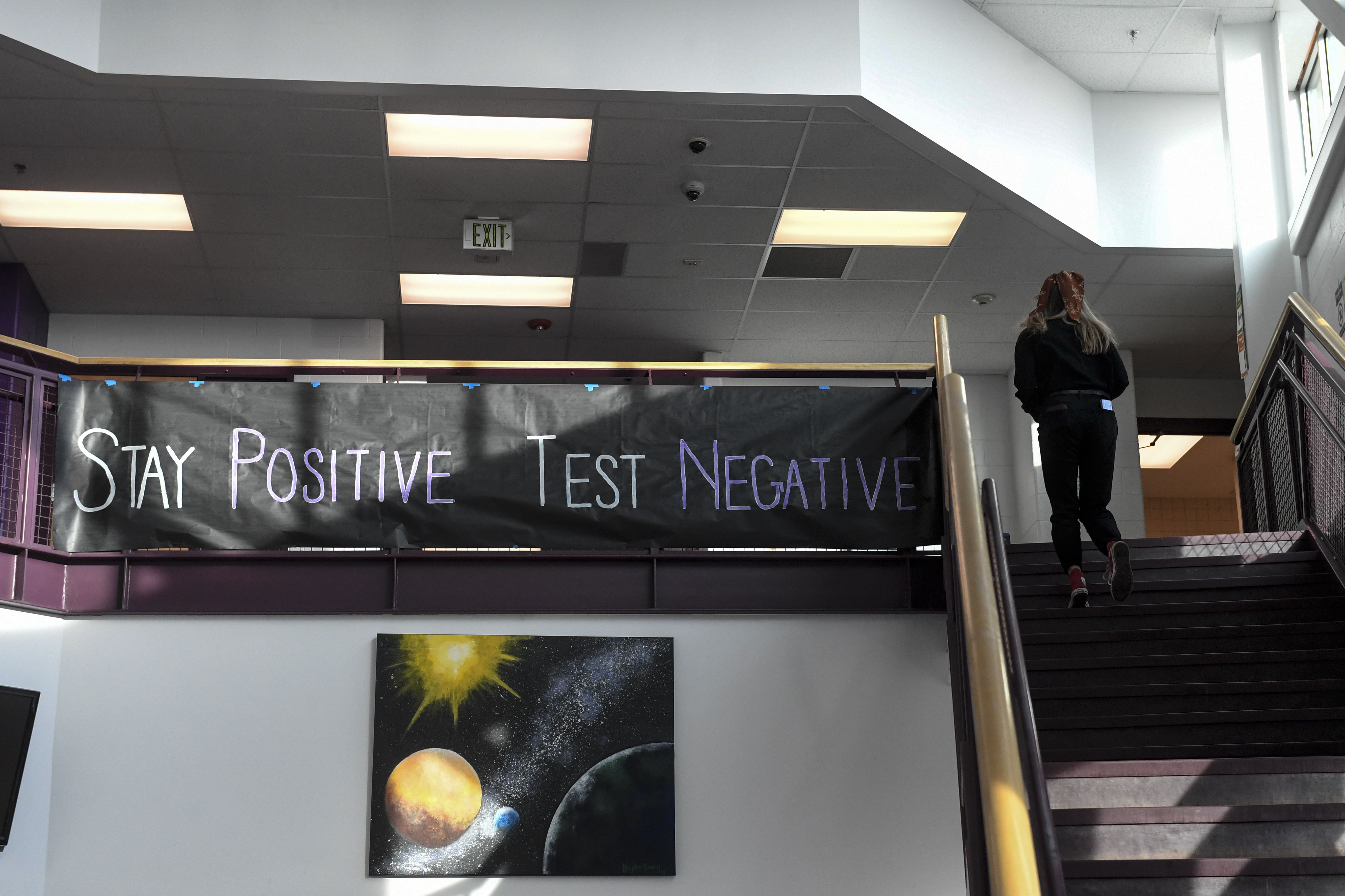 """A large banner hangs from a railing at the top of the stairs in a high school. It reads, """"Stay positive, test negative."""""""