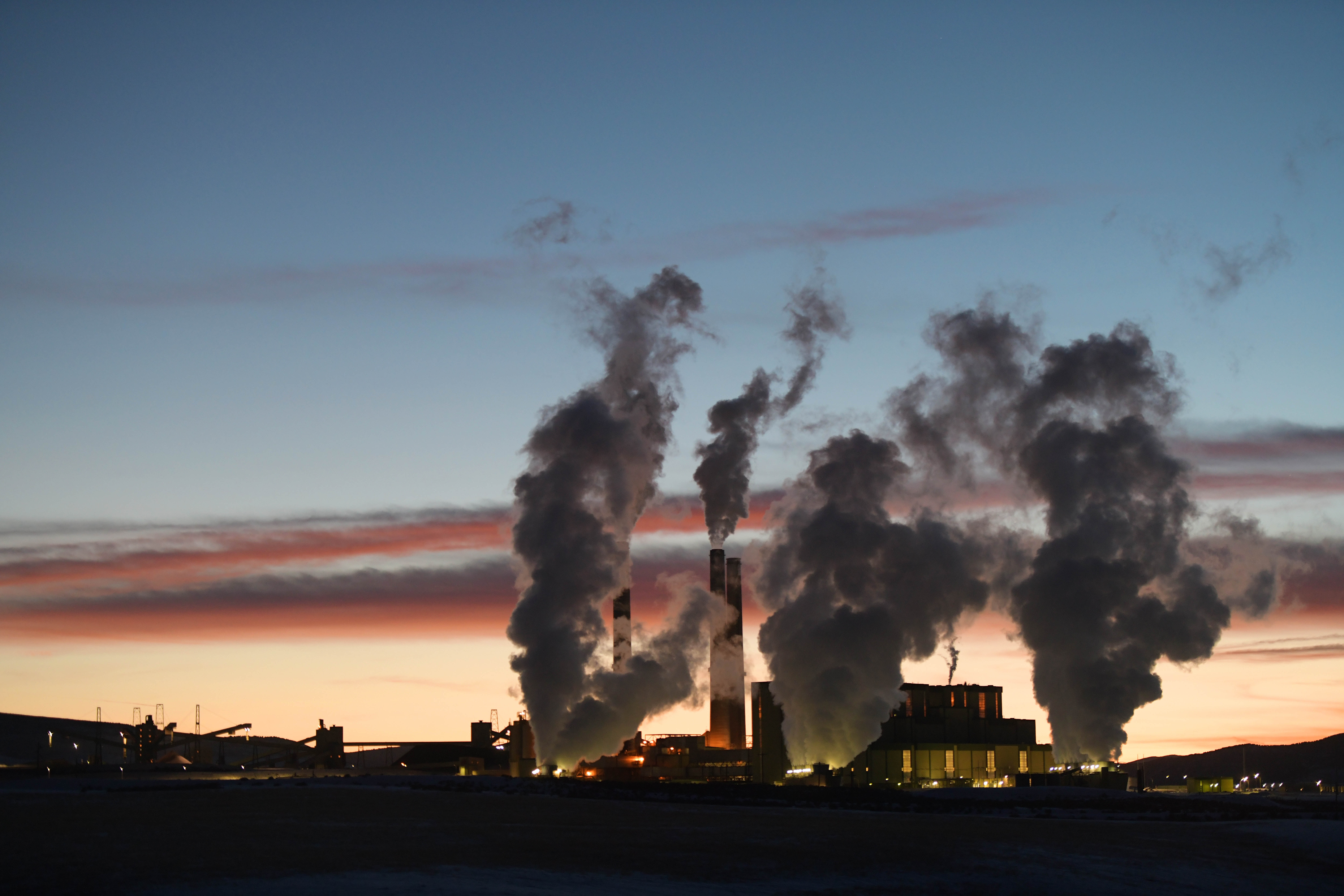 Plums of smoke rise from from the Craig Station coal-burning power plant, against a setting sun.