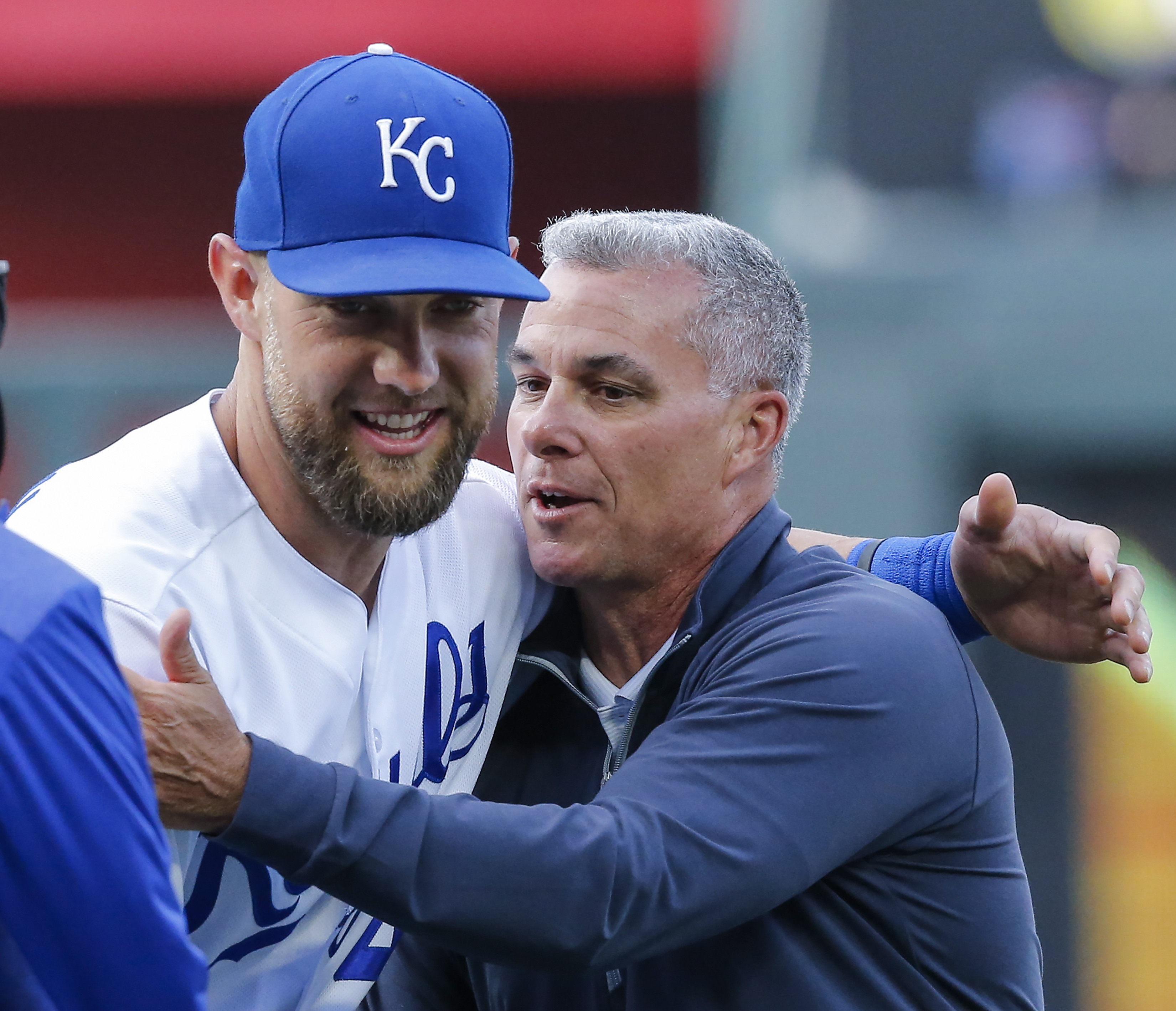 Dayton Moore shares a word with Alex Gordon before a game in 2019