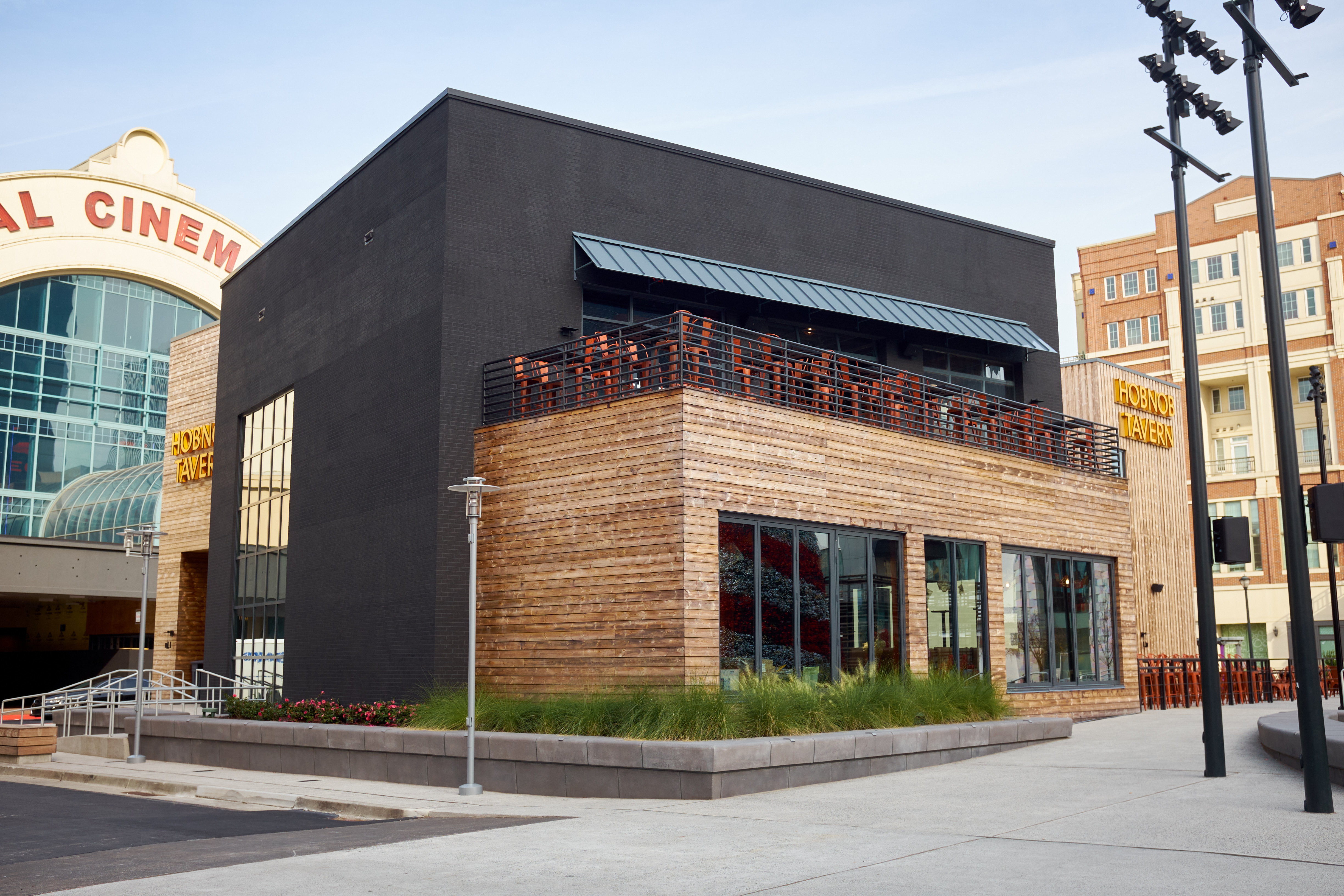 The black concrete and wood front exterior of Hobnob Neighborhood Tavern at Atlantic Station. A second story patios includes red metal chairs and tables overlooking the small central park of the complex in Midtown Atlanta.