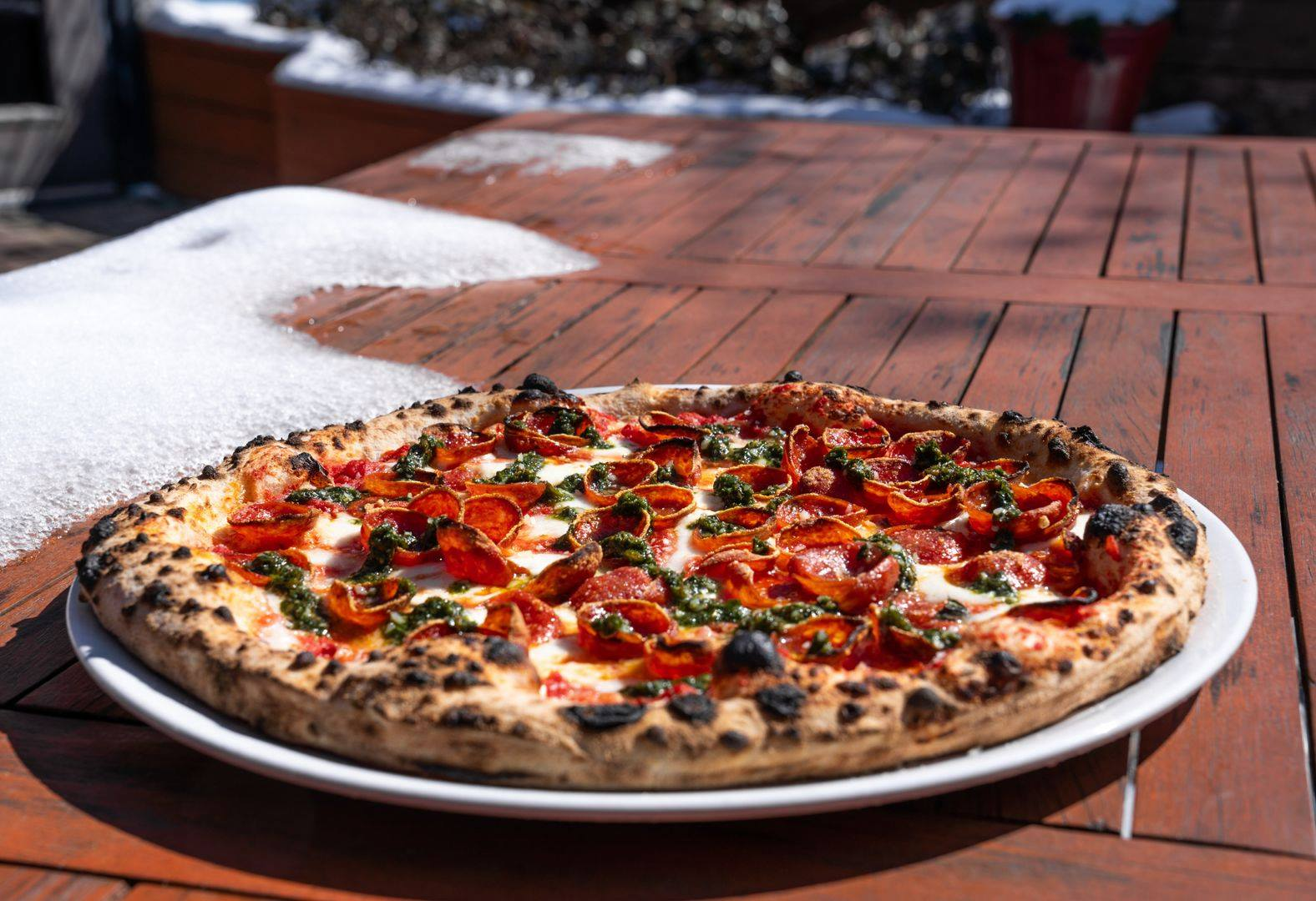 a pepperoni pizza resting on picnic table outdoors on a sunny day