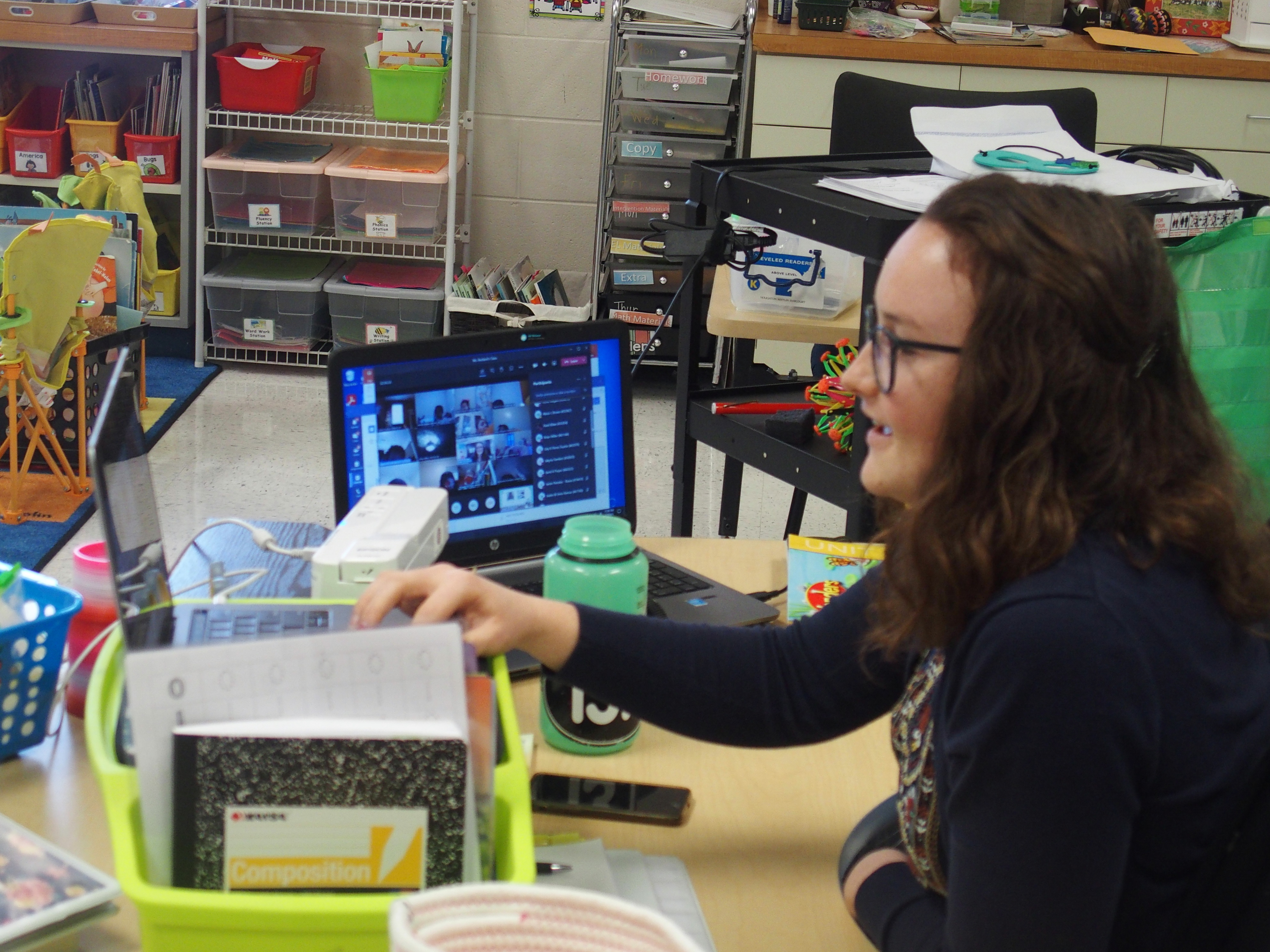 A teacher has two laptops set up at her classroom desk so she can instruct and see her students on videoconference.