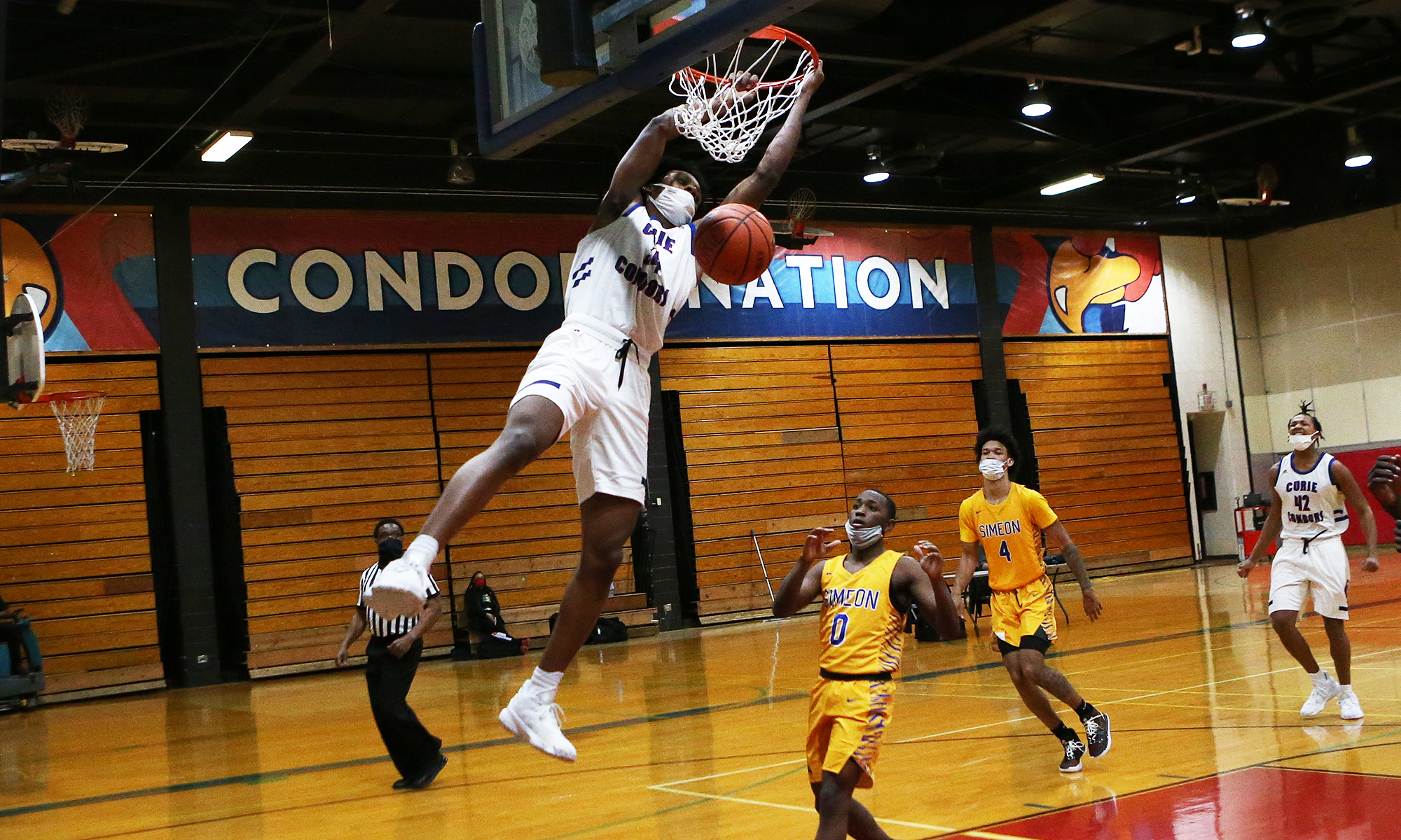 Curie's Jermell Grigsby dunks as the Condors host Simeon.