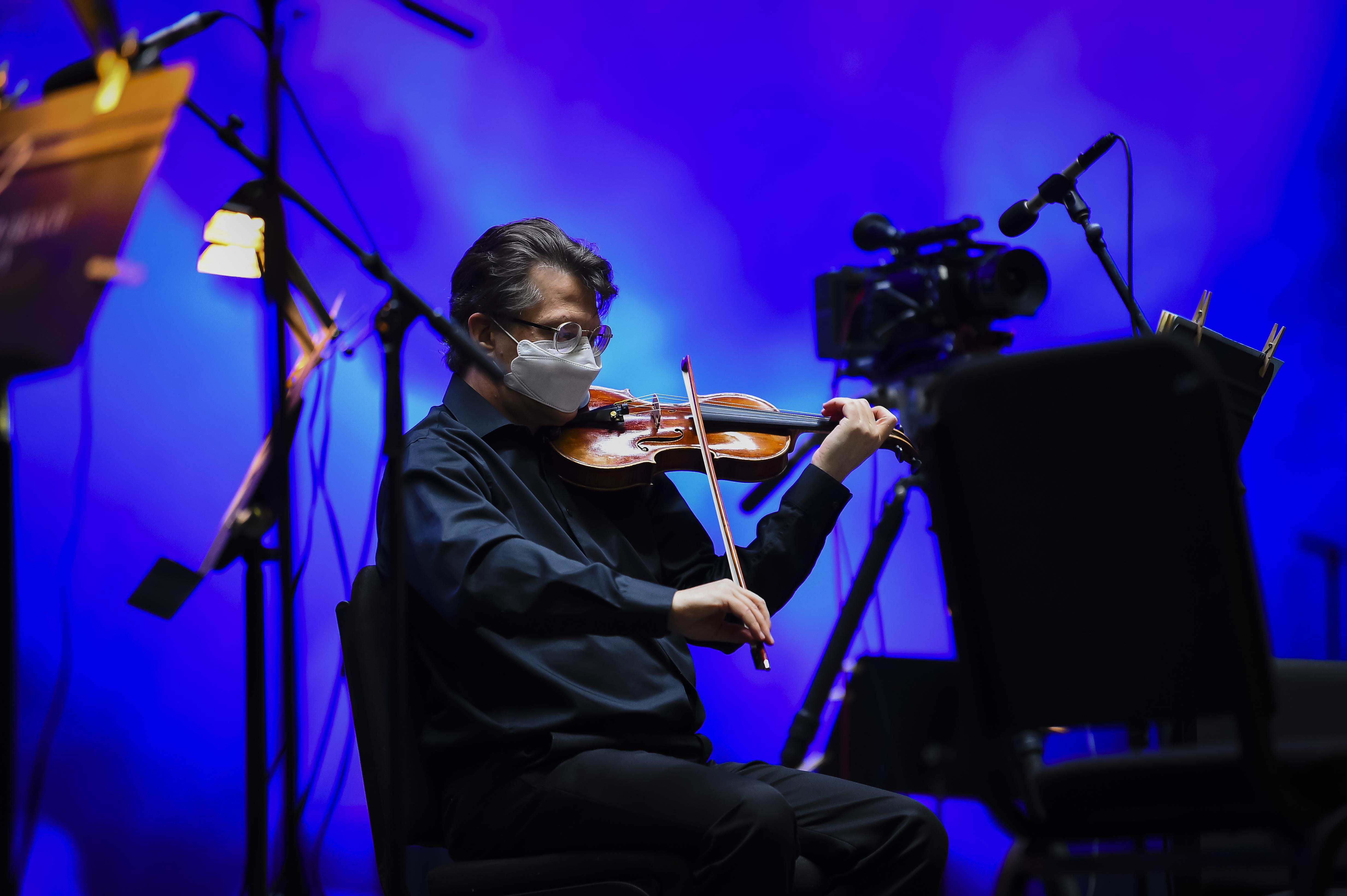 A masked violinist onstage.