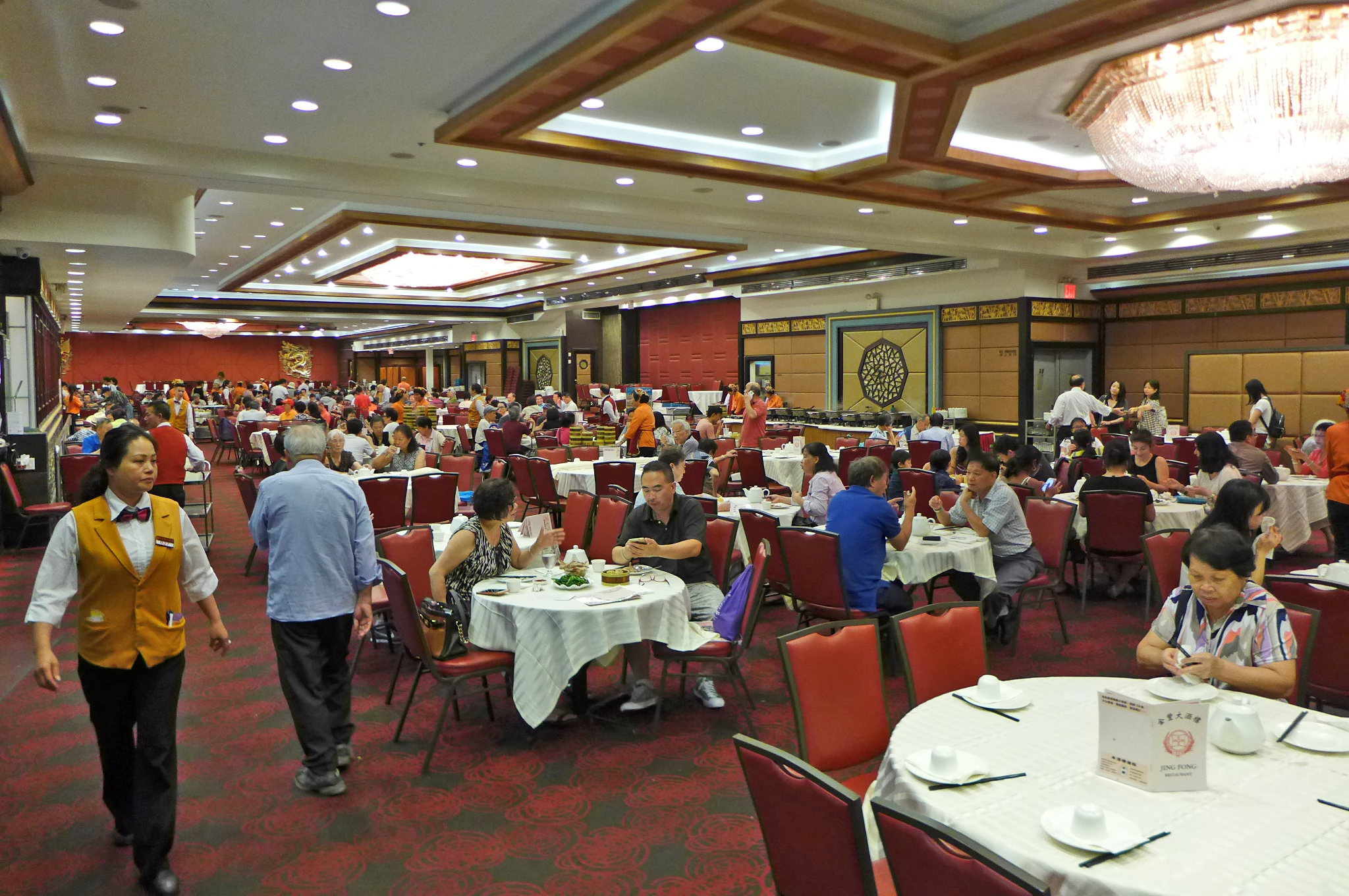 Jing Fong's dining room with large, communal round tables and a red-and-green floor is filled with diners.