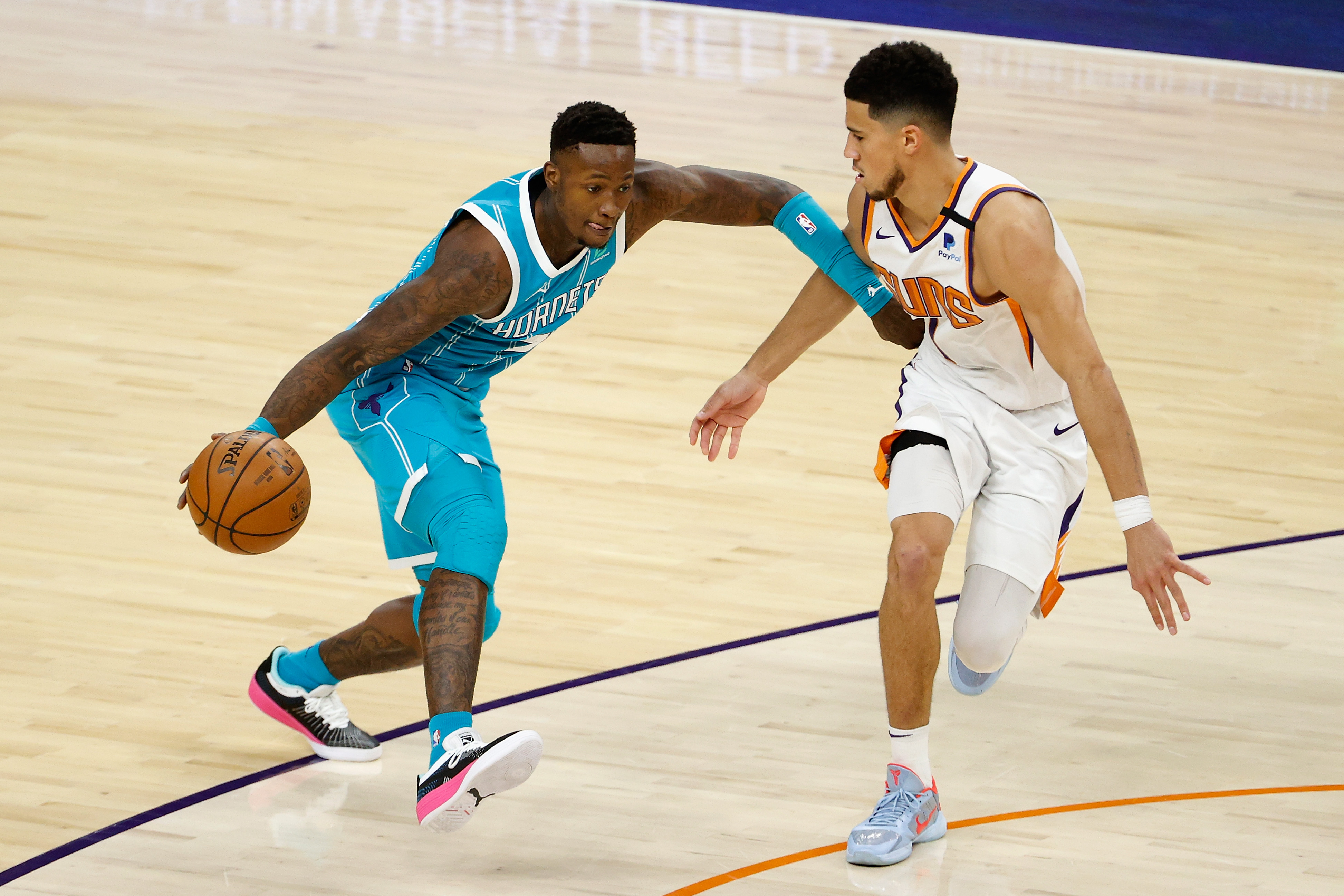 Terry Rozier of the Charlotte Hornets handles the ball against Devin Booker of the Phoenix Suns during the first half of the NBA game at Phoenix Suns Arena on February 24, 2021 in Phoenix, Arizona.