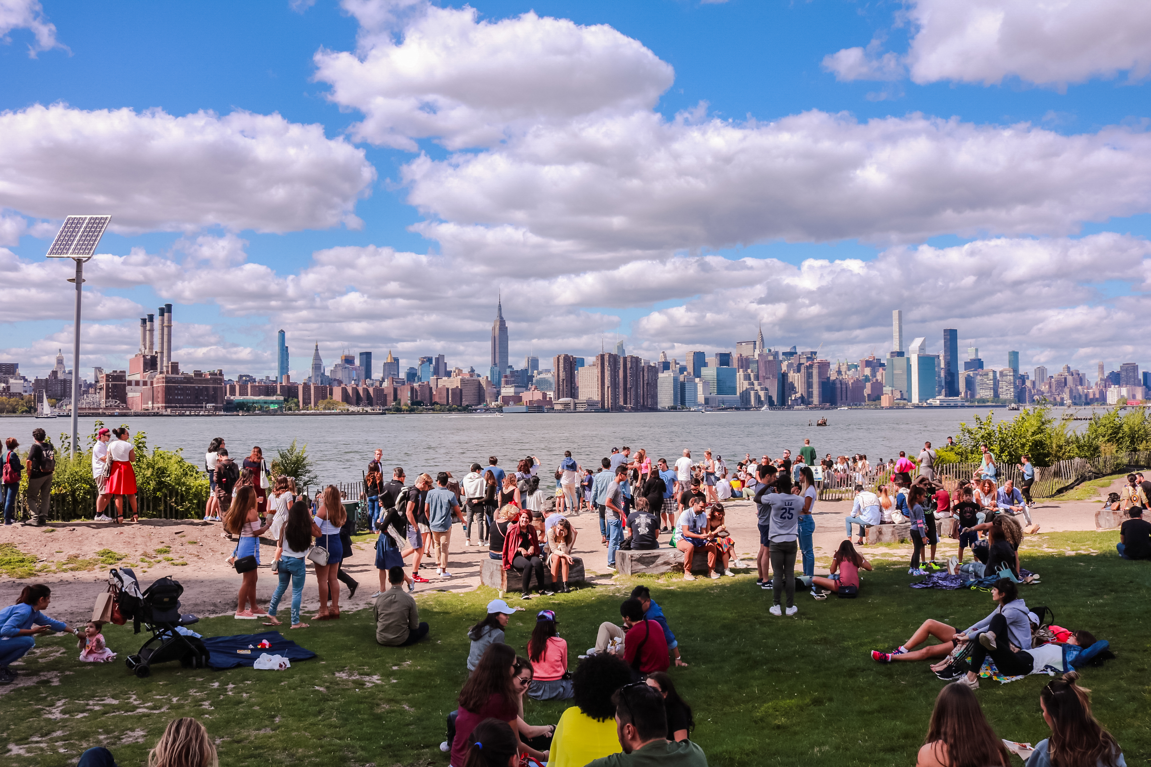 A group of people sitting on a green lawn looking at the Manhattan skyline and the East River in front of them