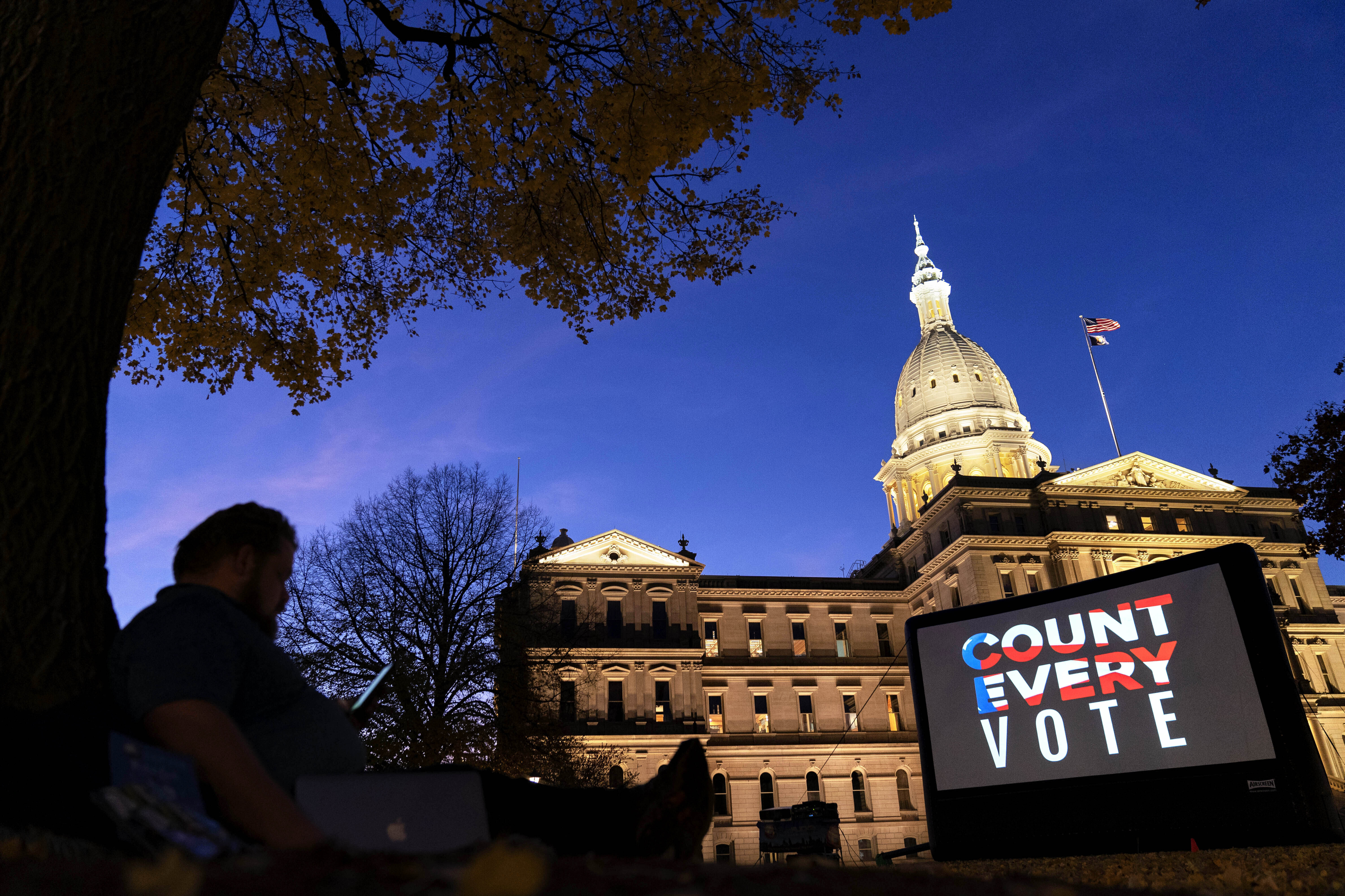 """In this Nov. 6, 2020, file photo, the phrase """"Count Every Vote"""" is displayed on a large screen, organized by an advocacy group in front of thesState Capitol while election results in several states had yet to be finalized, in Lansing, Mich."""