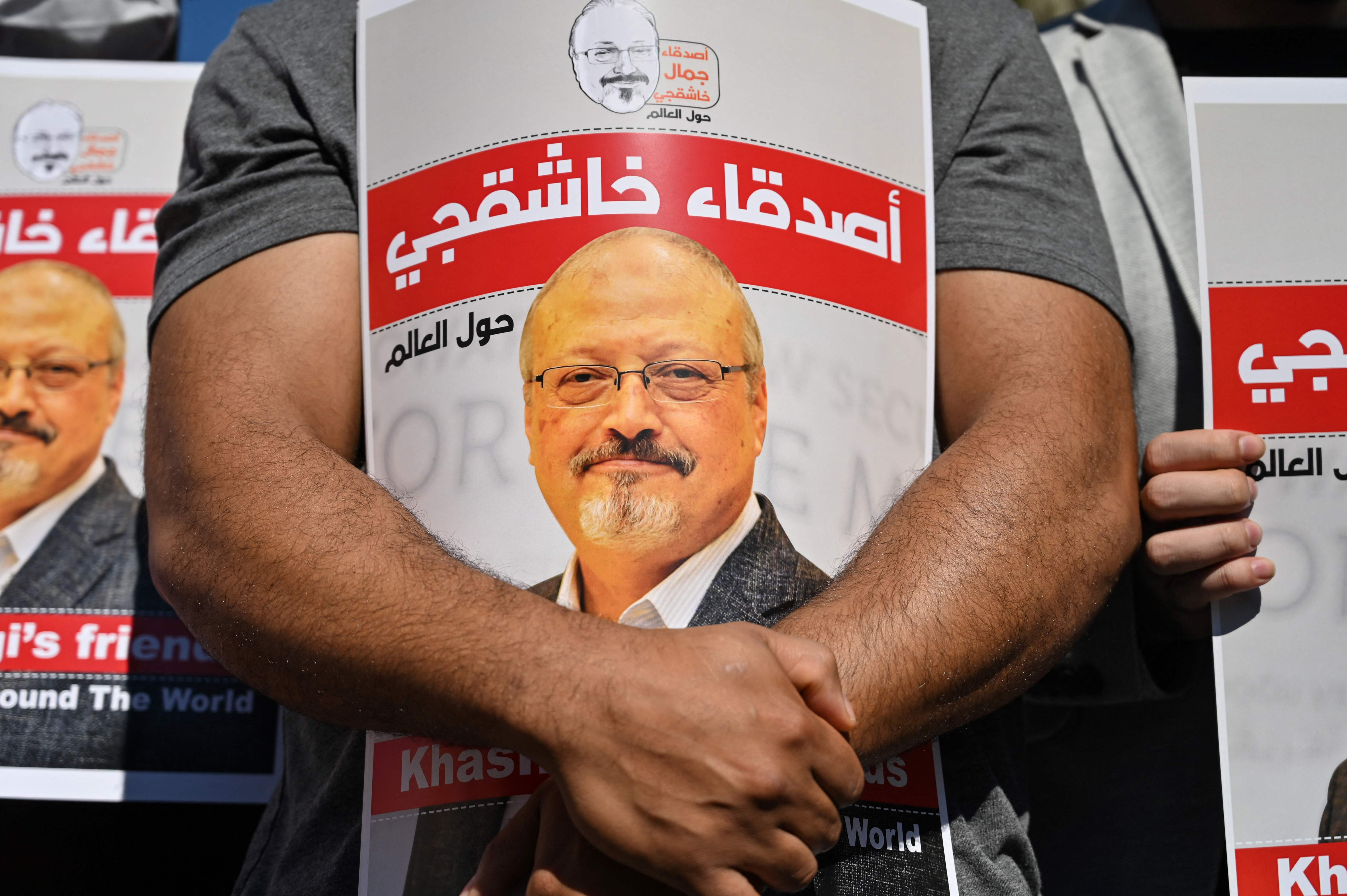 In this file photo taken on October 02, 2020, friends of murdered Saudi journalist Jamal Khashoggi hold posters bearing his picture as they attend an event marking the second-year anniversary of his assassination in front of Saudi Arabia Istanbul Consulate.