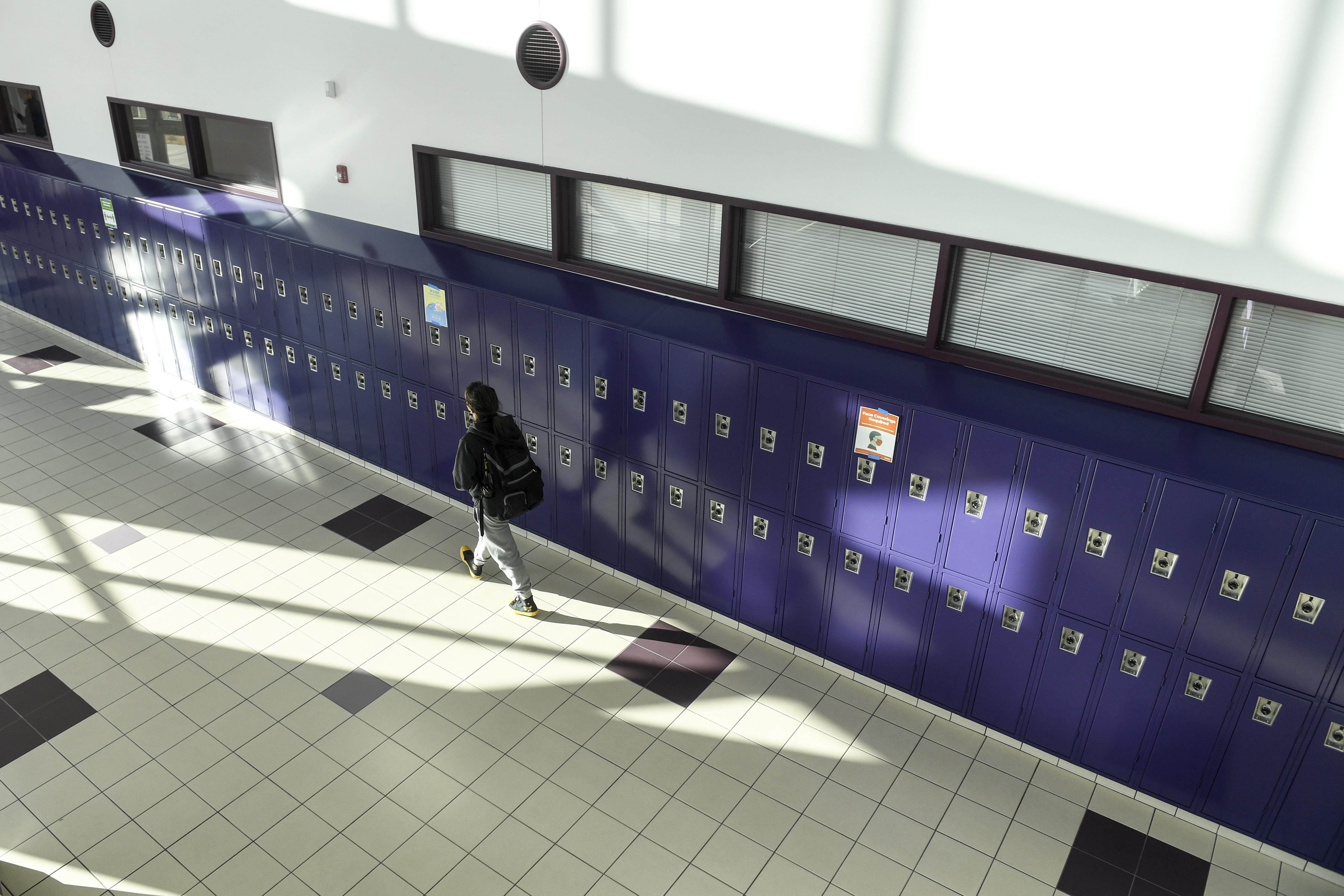 A high school student walks in an empty hallway past a row of purple lockers.