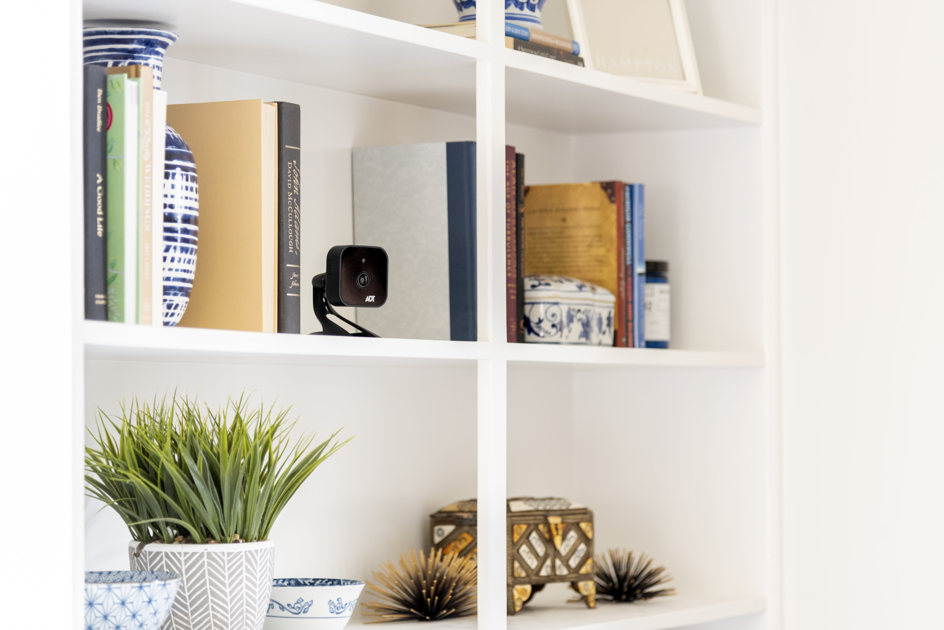 An ADT security camera sits on a white bookshelf with colorful books and planters.
