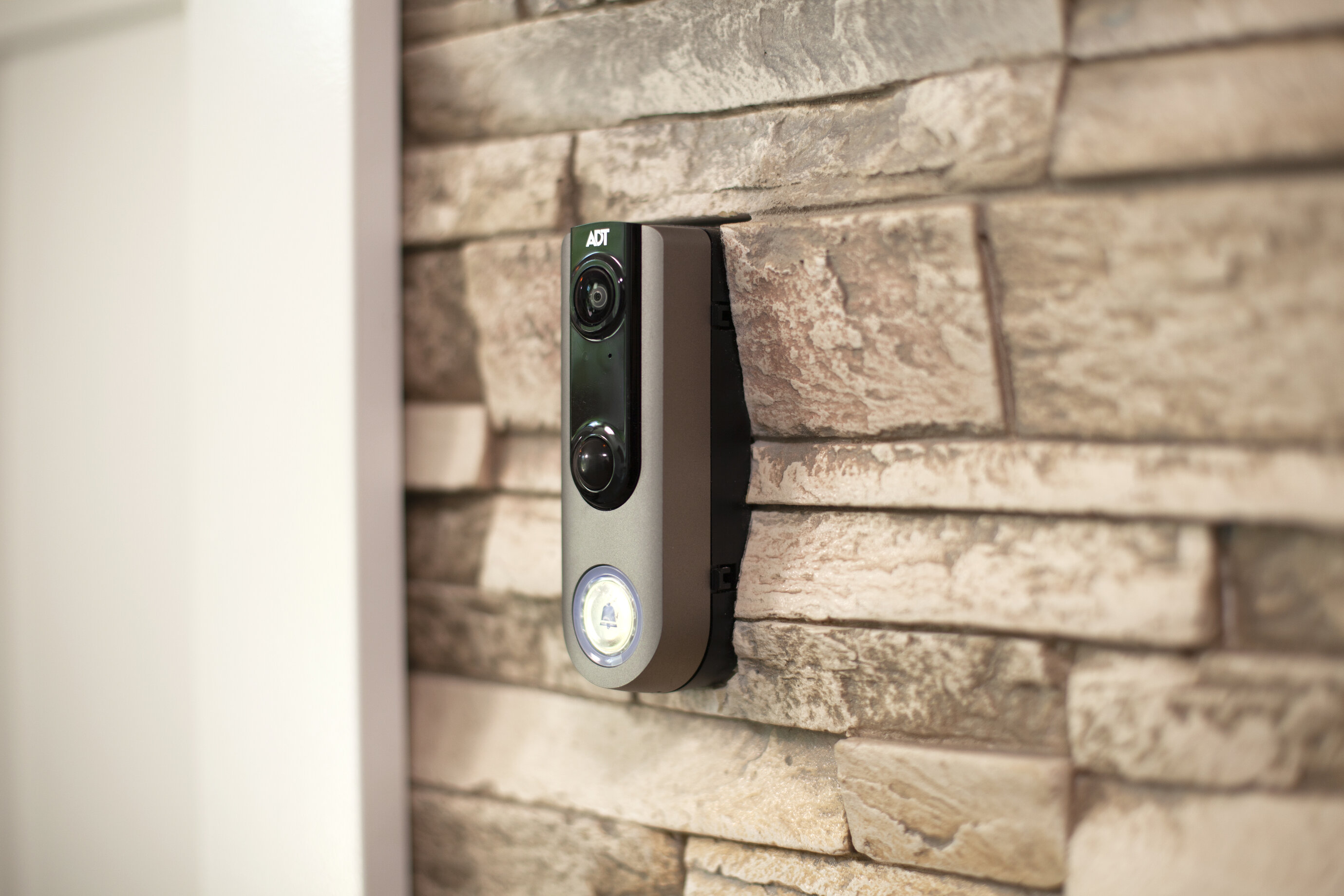 An ADT doorbell to the right of a white door on the exterior of a home with stone details.