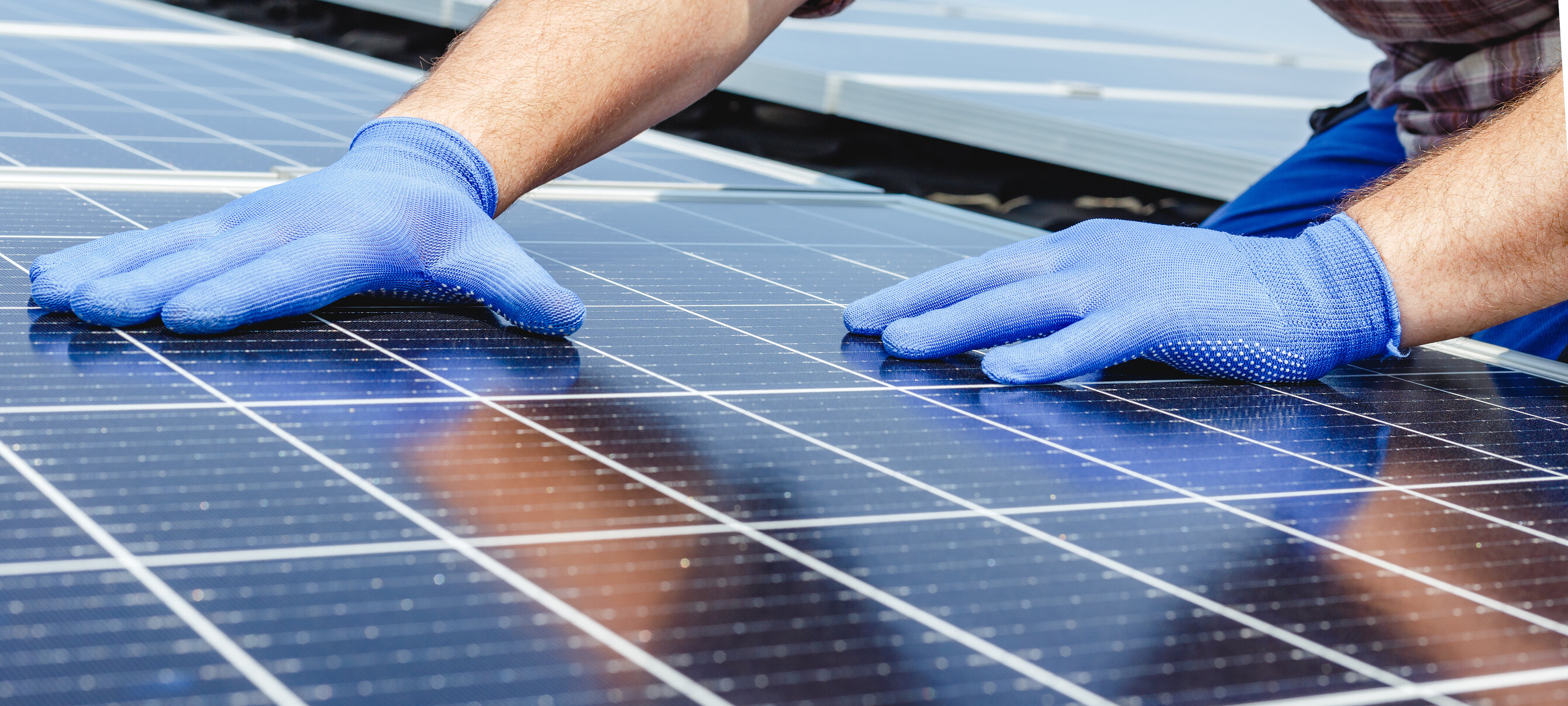 A close-up of a man wearing blue gloves installing solar panels.