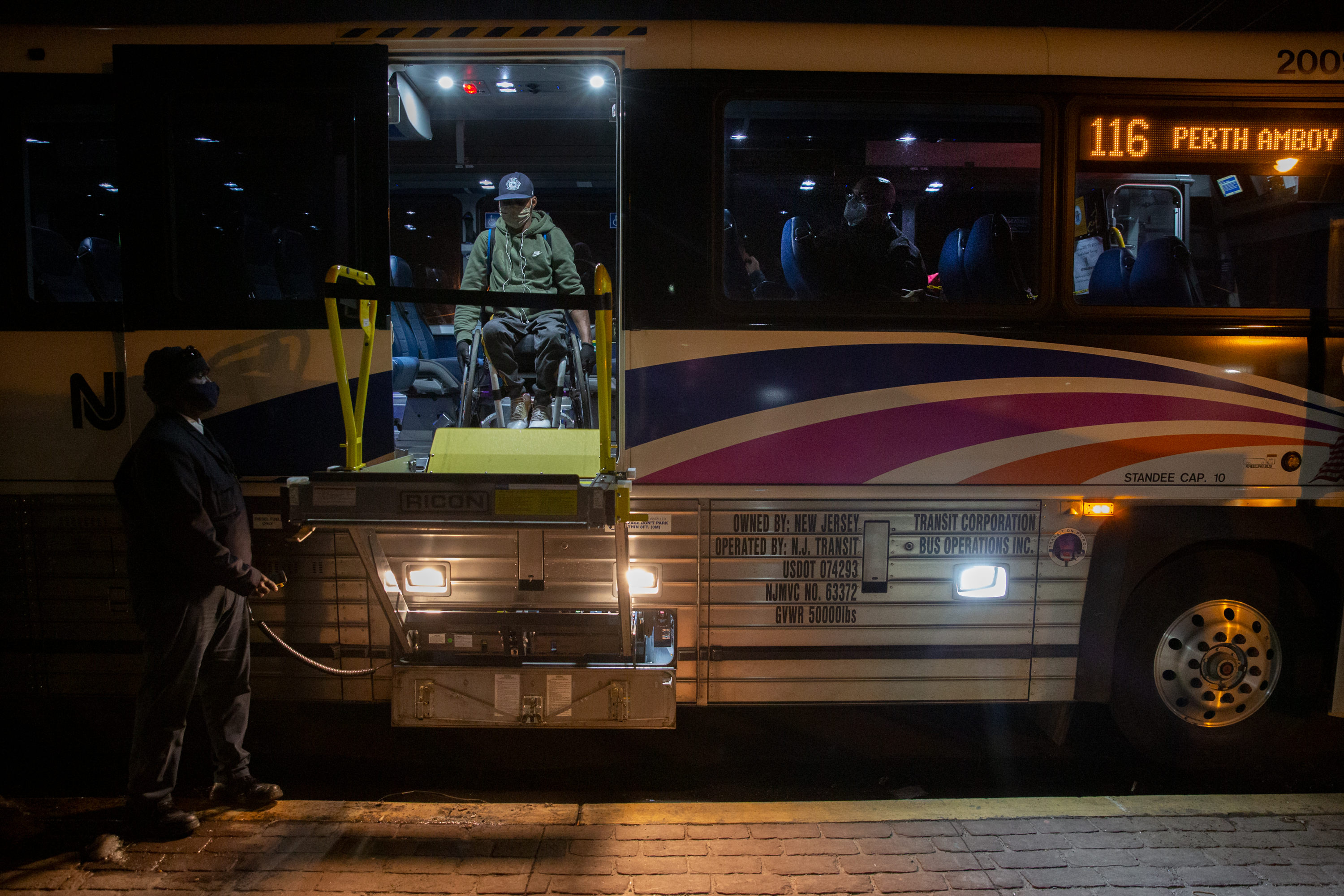 A New Jersey Transit bus driver helps Saheed Adebayo Aare disembark in Carteret his three-hour trip to work, Feb. 24, 2021.