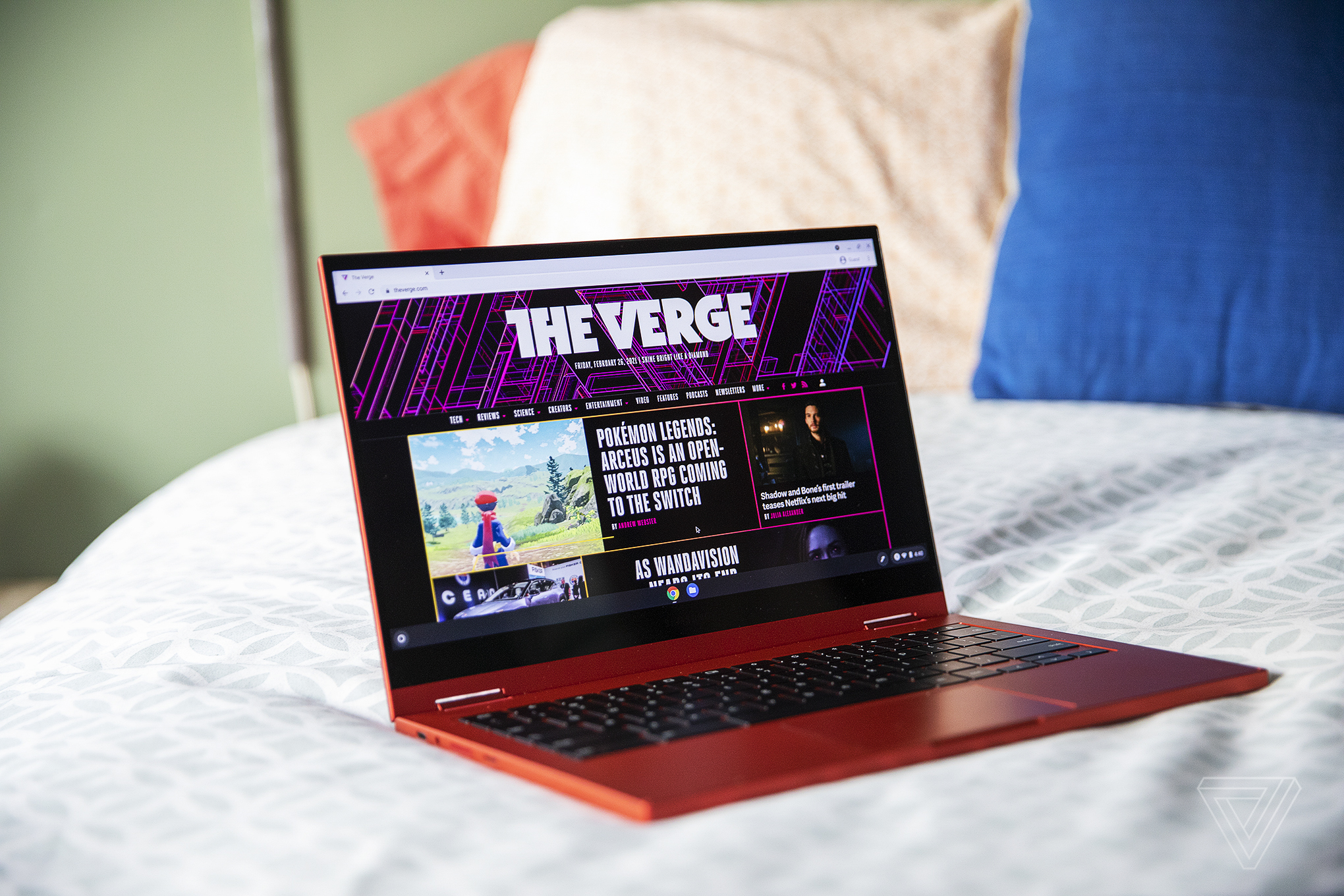 The Samsung Galaxy Chromebook open, angled slightly to the right on the corner of a bed. The screen displays The Verge homepage.