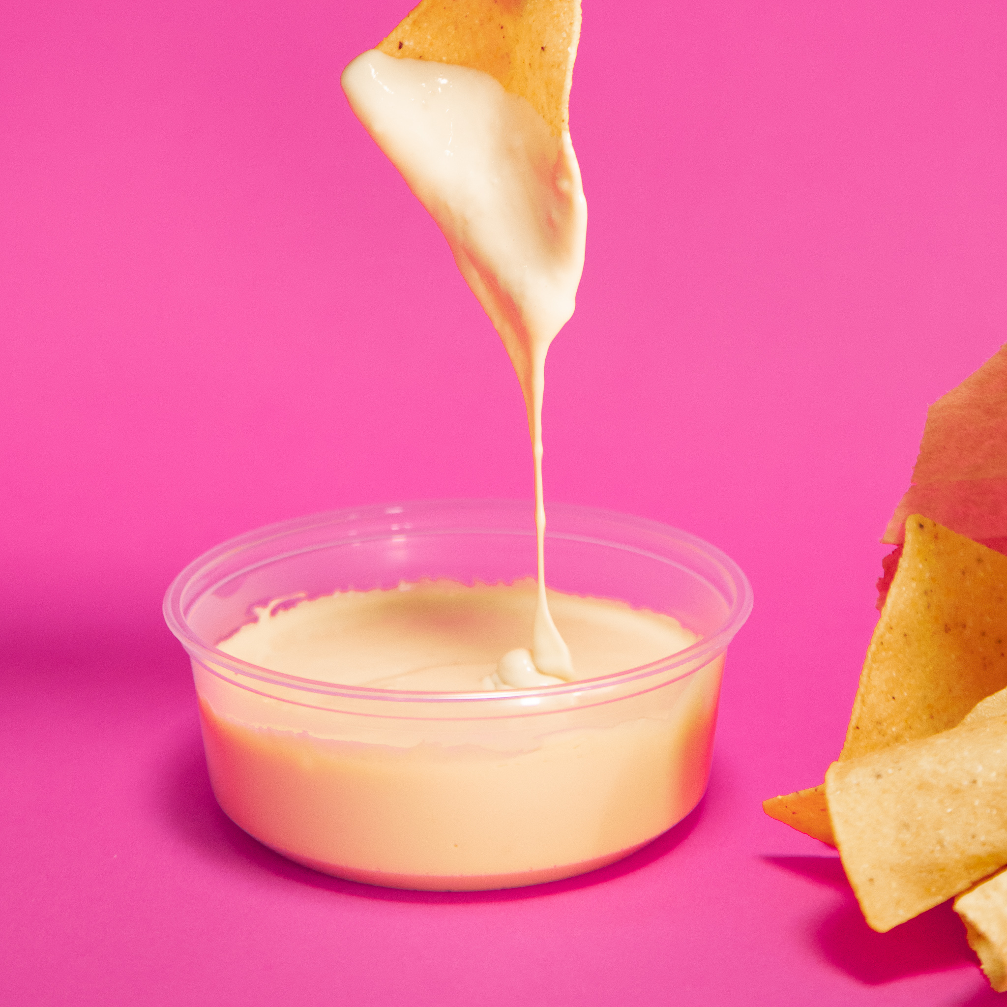 Yellow queso drips from a tortilla chip above a plastic container of cheese dip next to a bag of tortilla chips from the Queso Shop in Atlanta