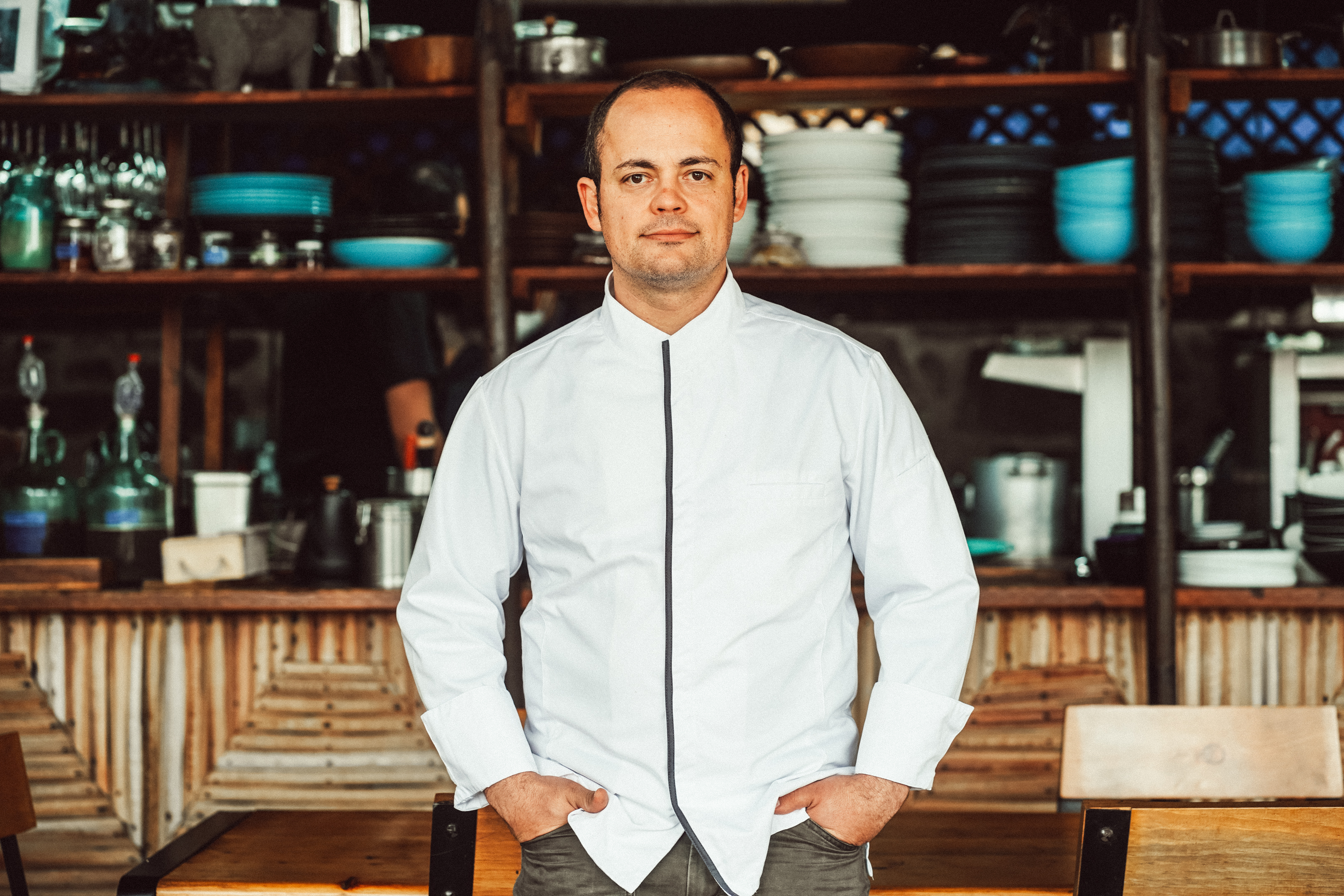 Chef Roberto Alcocer stands with his hands inside his pockets in the dining room of Malva restaurant in the Valle de Guadalupe
