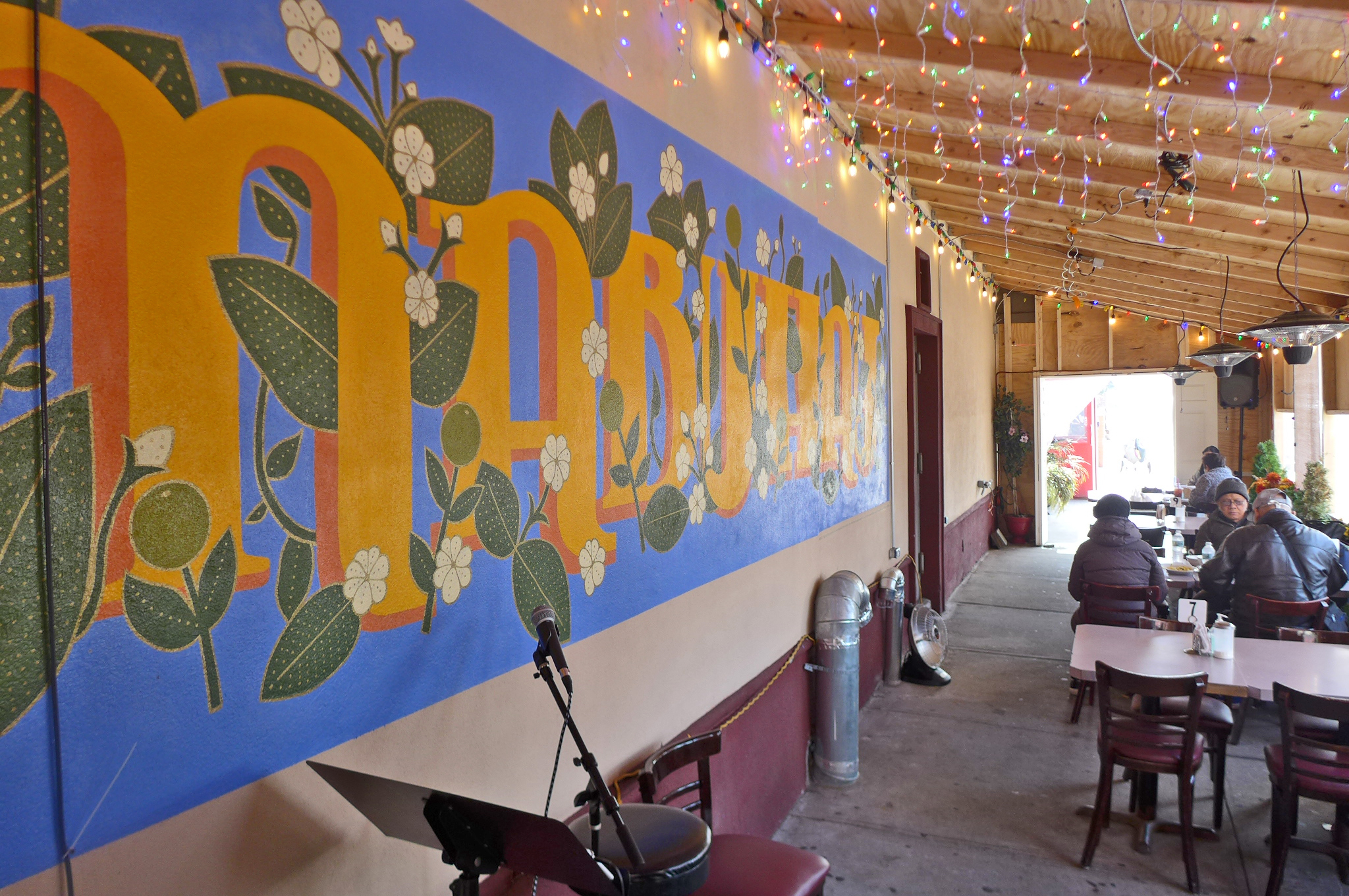 An outdoor seating area with mural on a wall to the left and customers seated at a table to the right.