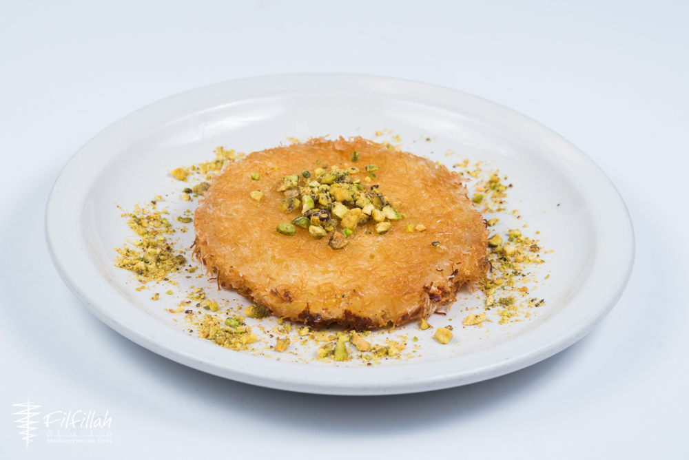 A white background and white plate offset a golden round of knafeh, with little crispy shreds of phyllo dough, more darkly crusted on the bottom, given a glistening sheen from the syrup, and garnished with chopped green pistachios