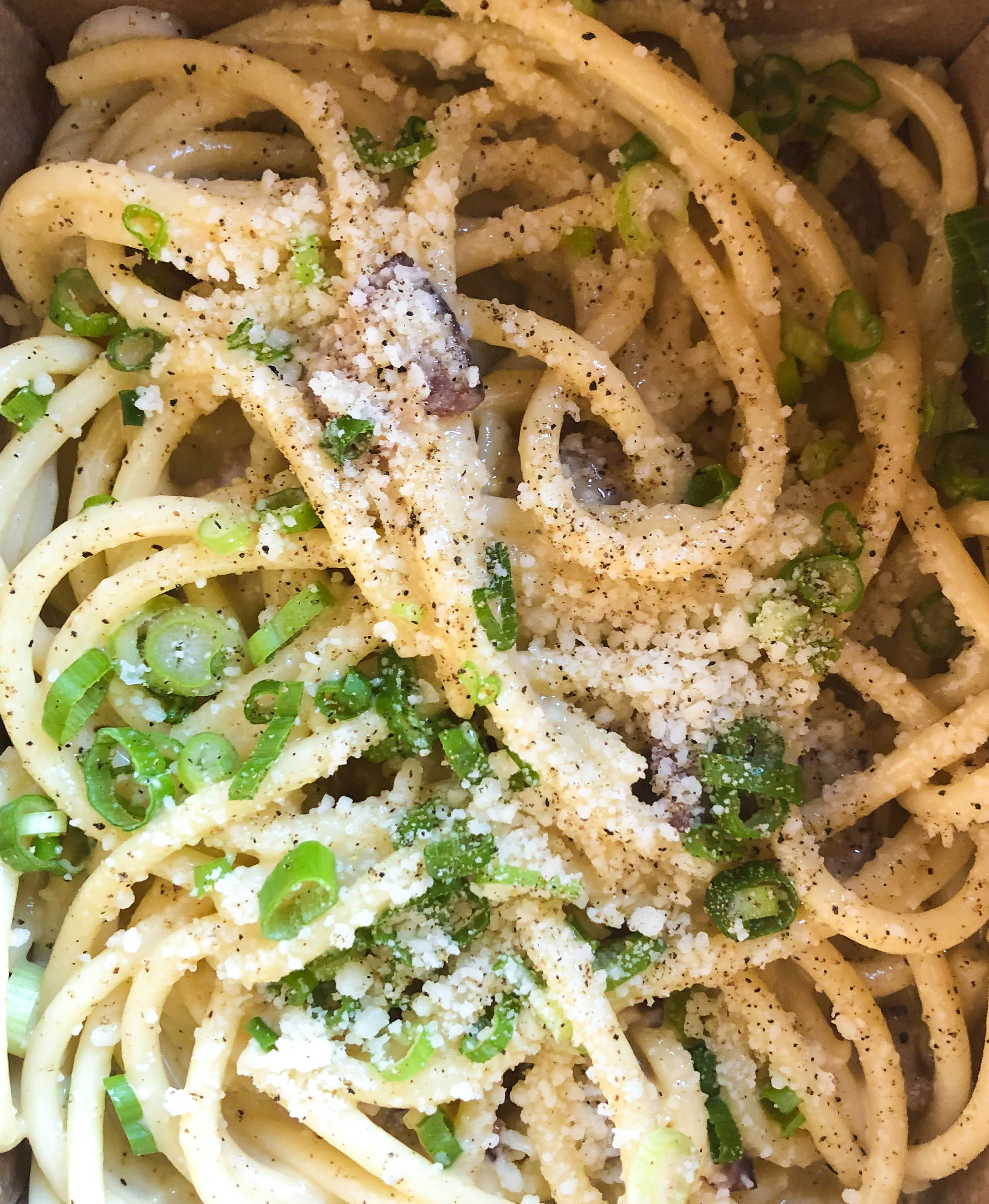 A close-up of tangles of pasta with shaved cheese and green onions at L'Unico