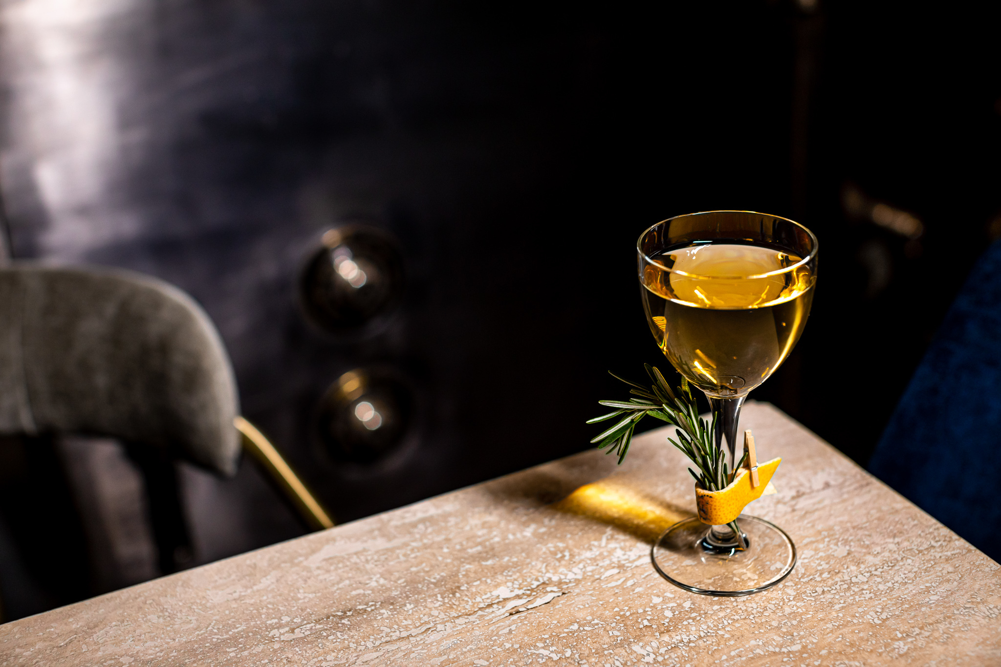 Mezcal and amontillado sherry cocktail Flashing Lights from the Shelby with a garnish of rosemary clip to the stem of the coup glass with a lemon peel