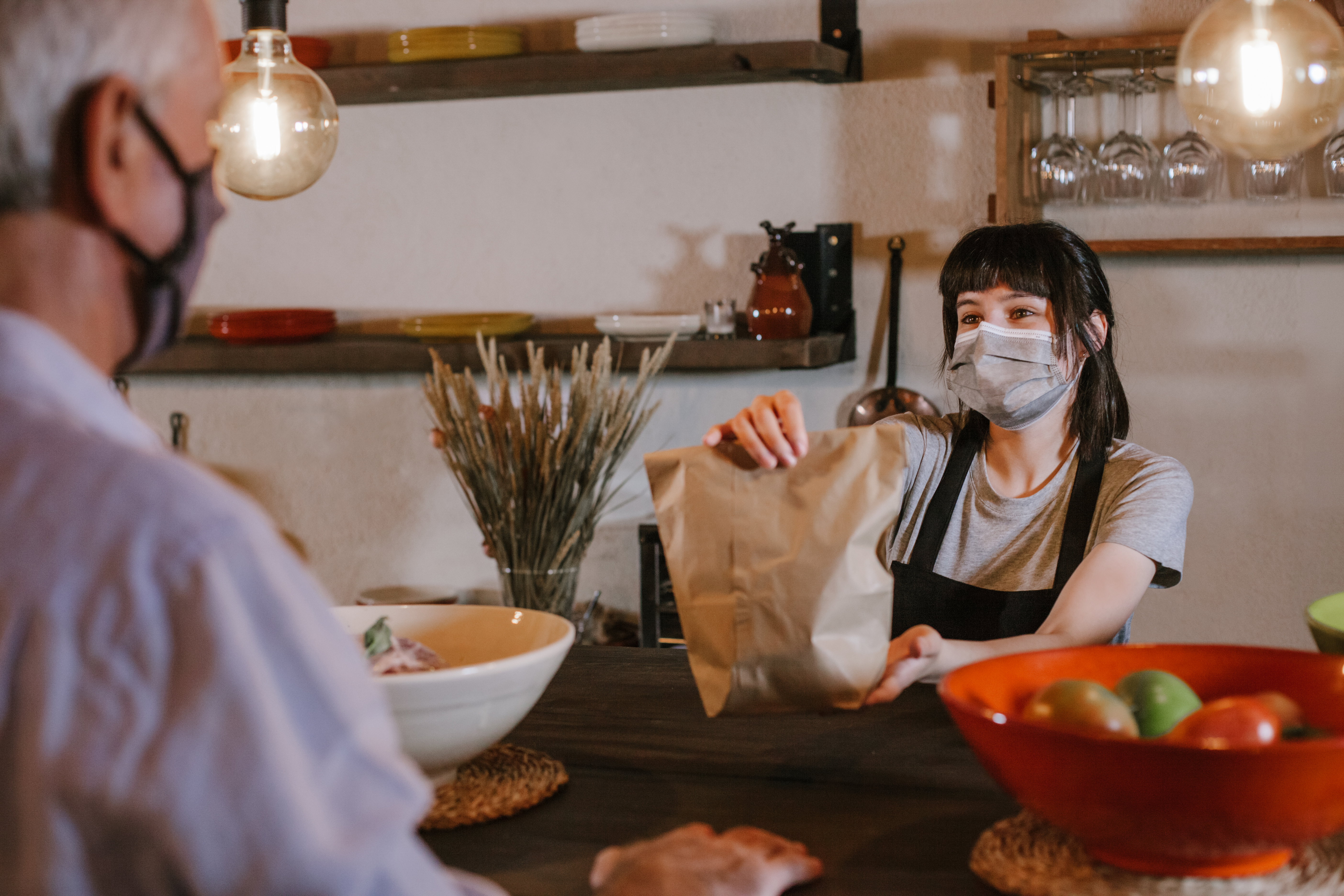 A masked restaurant workers passes a bag of food across a counter to a masked diner