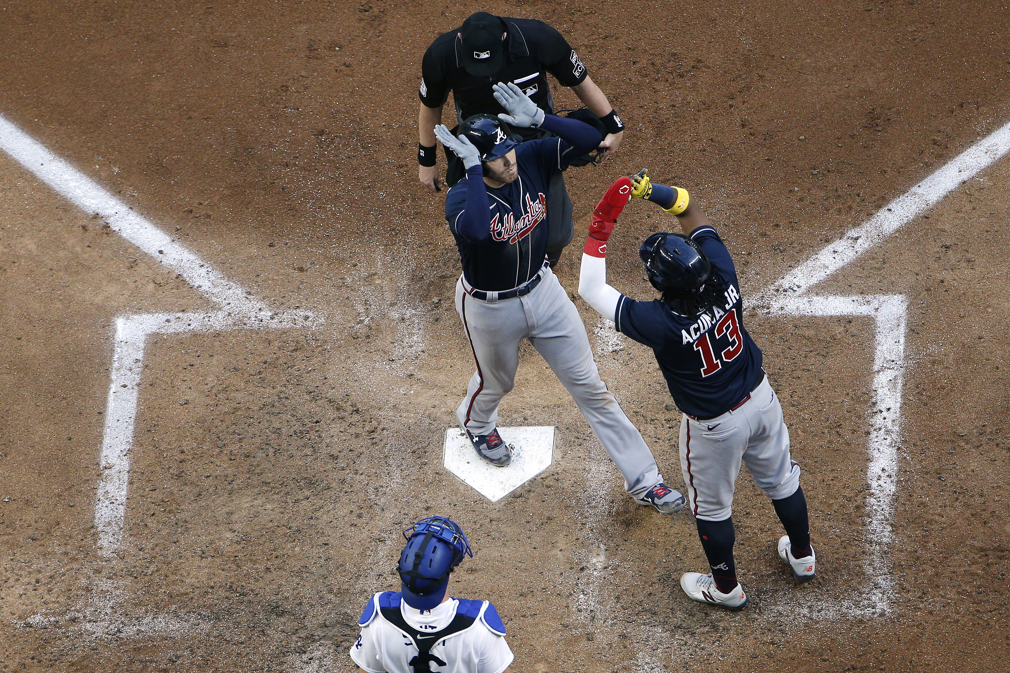 Freddie Freeman #5 of the Atlanta Braves is congratulated by Ronald Acuna Jr. #13 after hitting a two run home run against the Los Angeles Dodgers during the fourth inning in Game Two of the National League Championship Series at Globe Life Field on October 13, 2020 in Arlington, Texas.