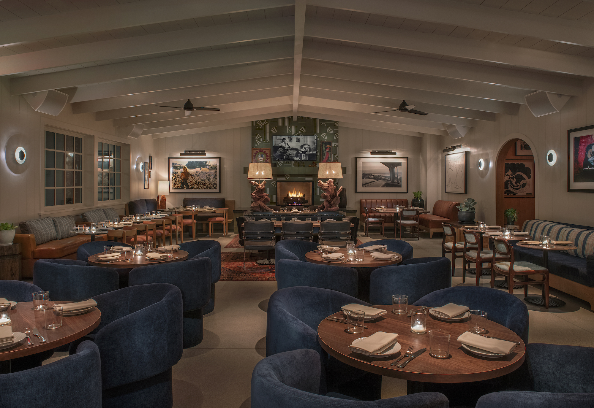 A dimly lit dining room with plush blue chairs around tight tables.