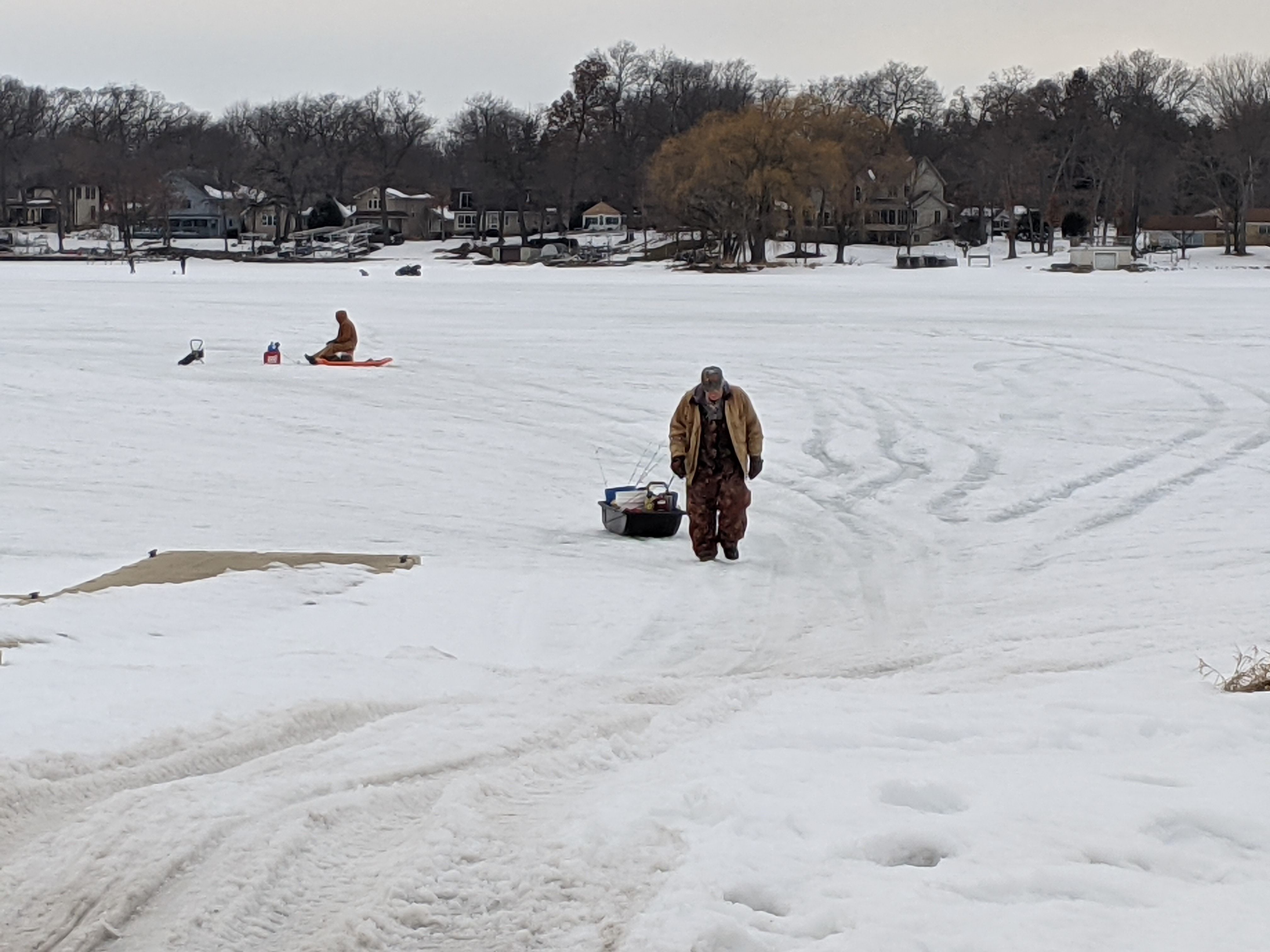 The weather has been warm enough to allow anglers to sit on a bucket outside on the ice, as these guys were Friday evening at Channel Lake; even with ice reaching depths of 18 inches in spots and weeks of heavy snow cover, significant winter fish kills are not expected around the Chicago area. Credit: Dale Bowman