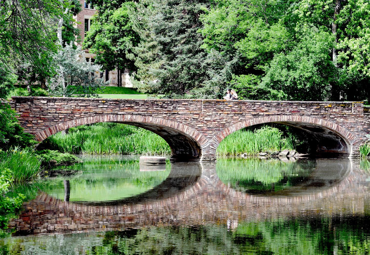 Two women cross the bridge over Varsity Pond on the University of Colorado Boulder campus on June 27, 2019.