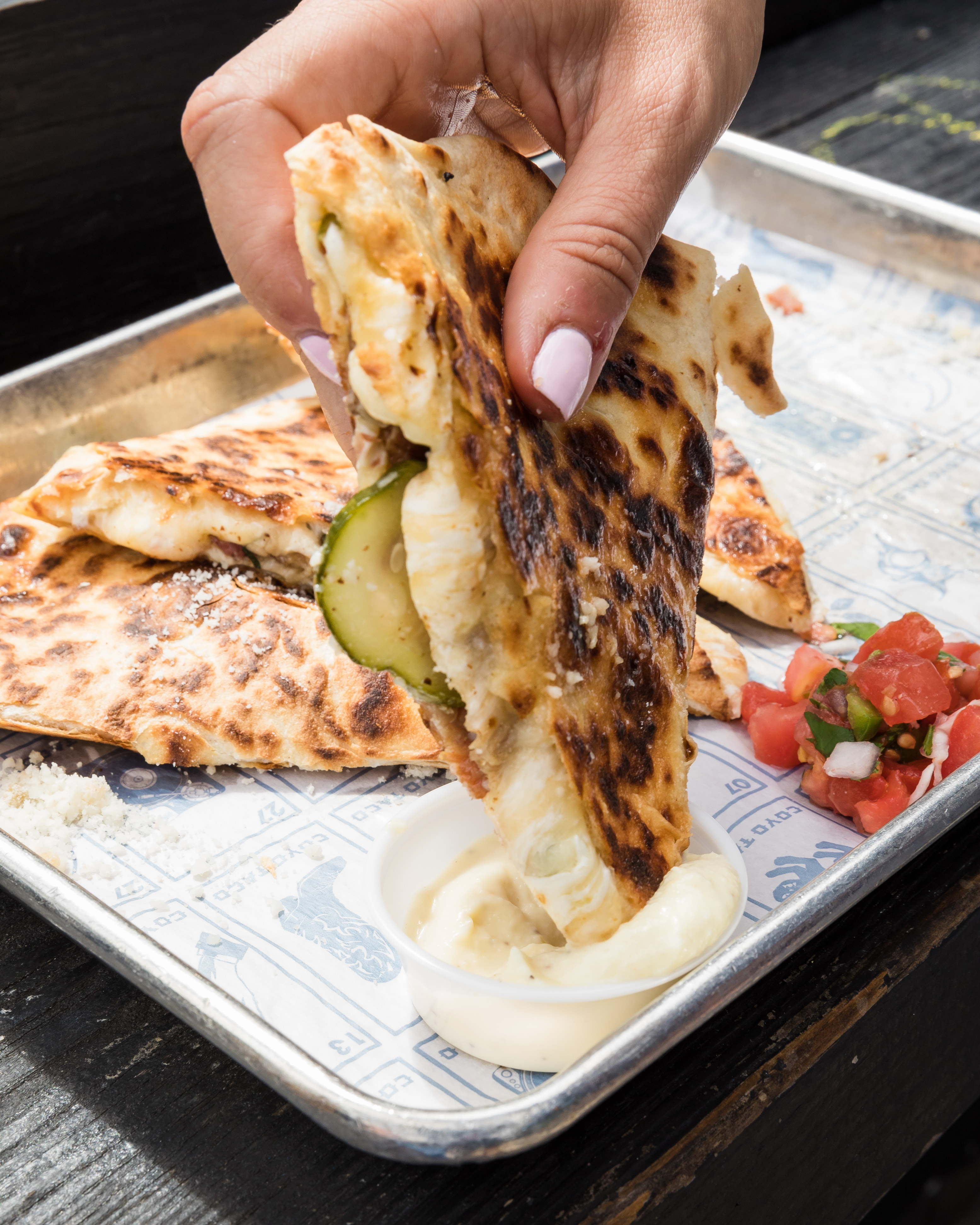 quesadilla being dipped into a sauce