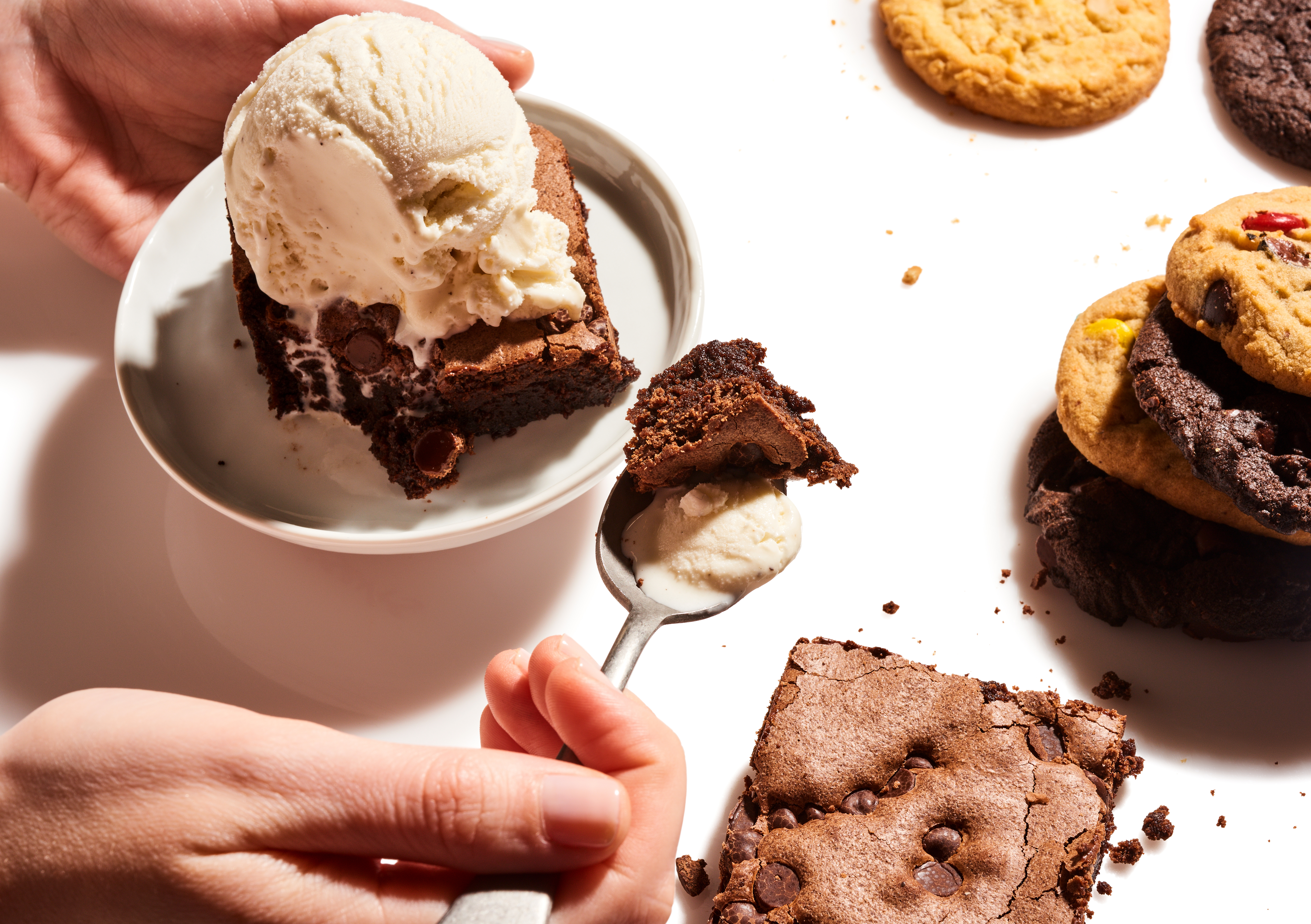 Hand holding a spoonful of brownie and vanilla ice cream next to a carton of vanilla ice cream containing a chocolate brownie topped with a scoop of vanilla ice cream. Chocolate chip cookies and brownie are scattered beside the carton from Insomnia Cookies