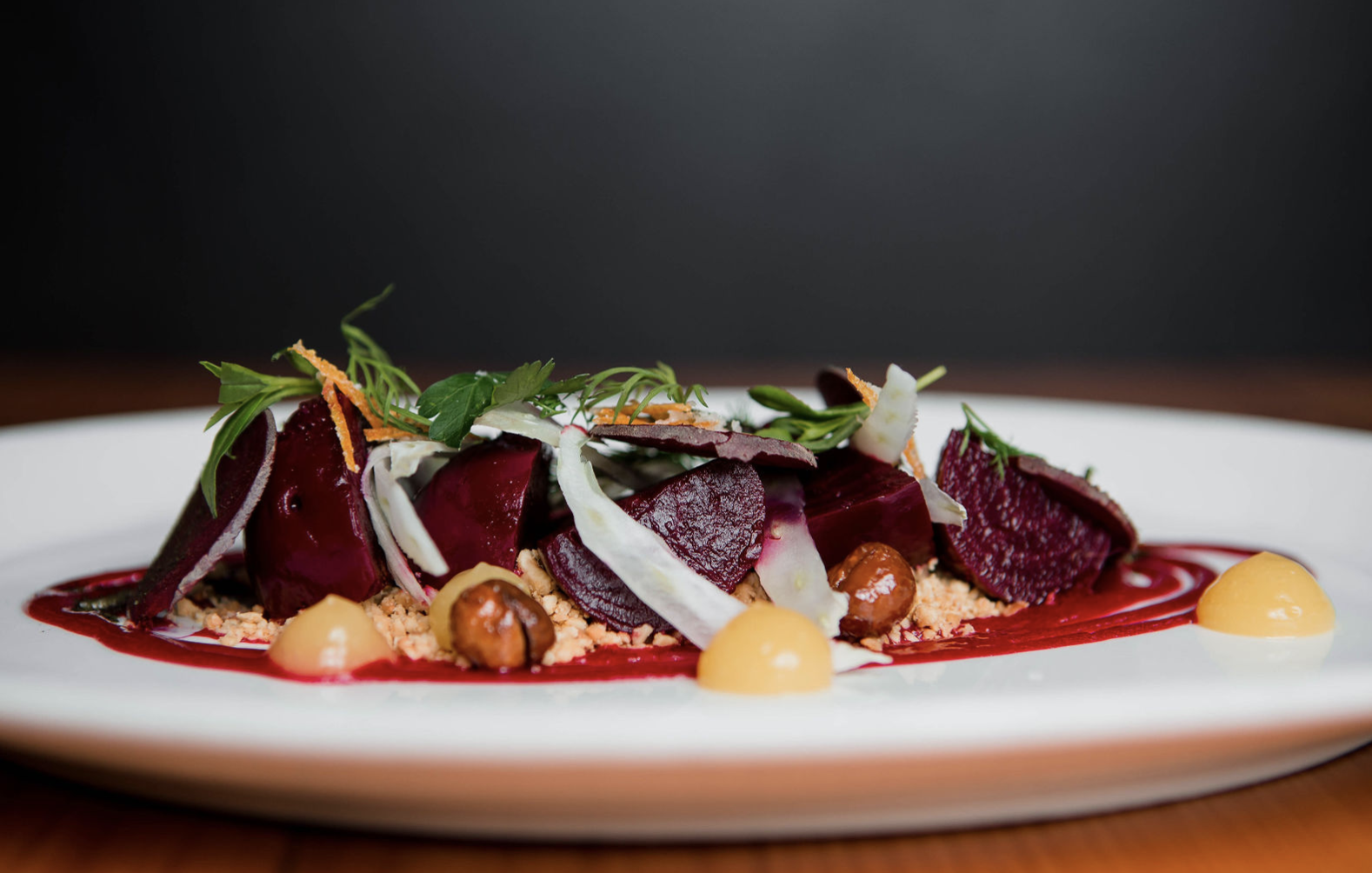 Roasted beets with citrus, fennel, and hazelnuts on a white plate at Local 360