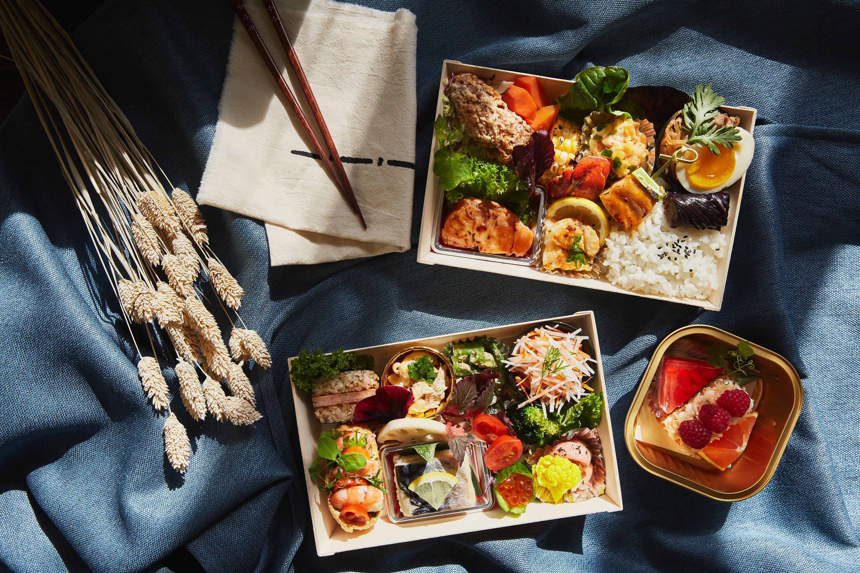 A pair of bento boxes shown from above in moody lighting, draped in blue cloth.