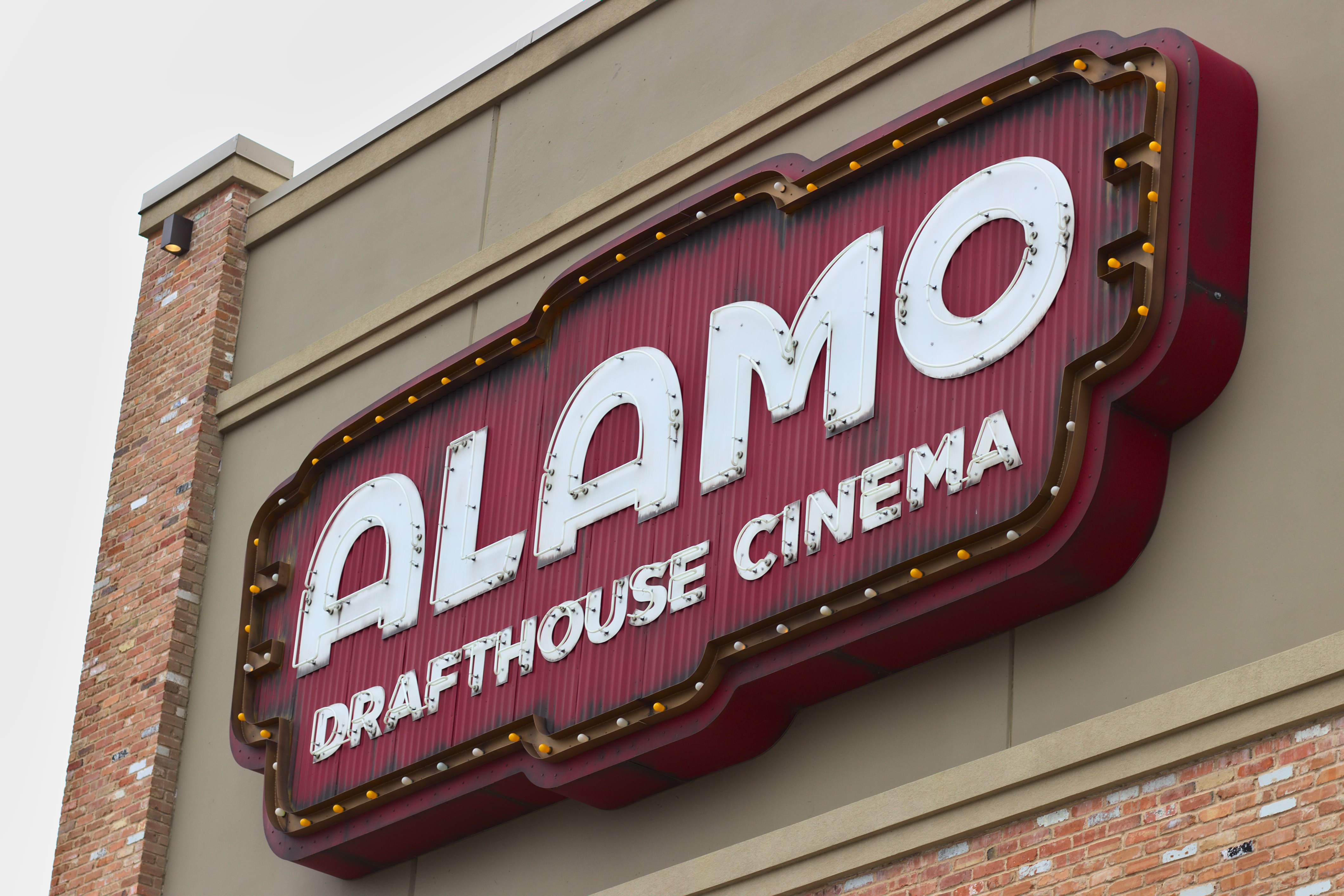 The brick and beige exterior of a building with a red and white sign, bordered with Edison bulbs, advertising the Alamo Drafthouse Cinema.