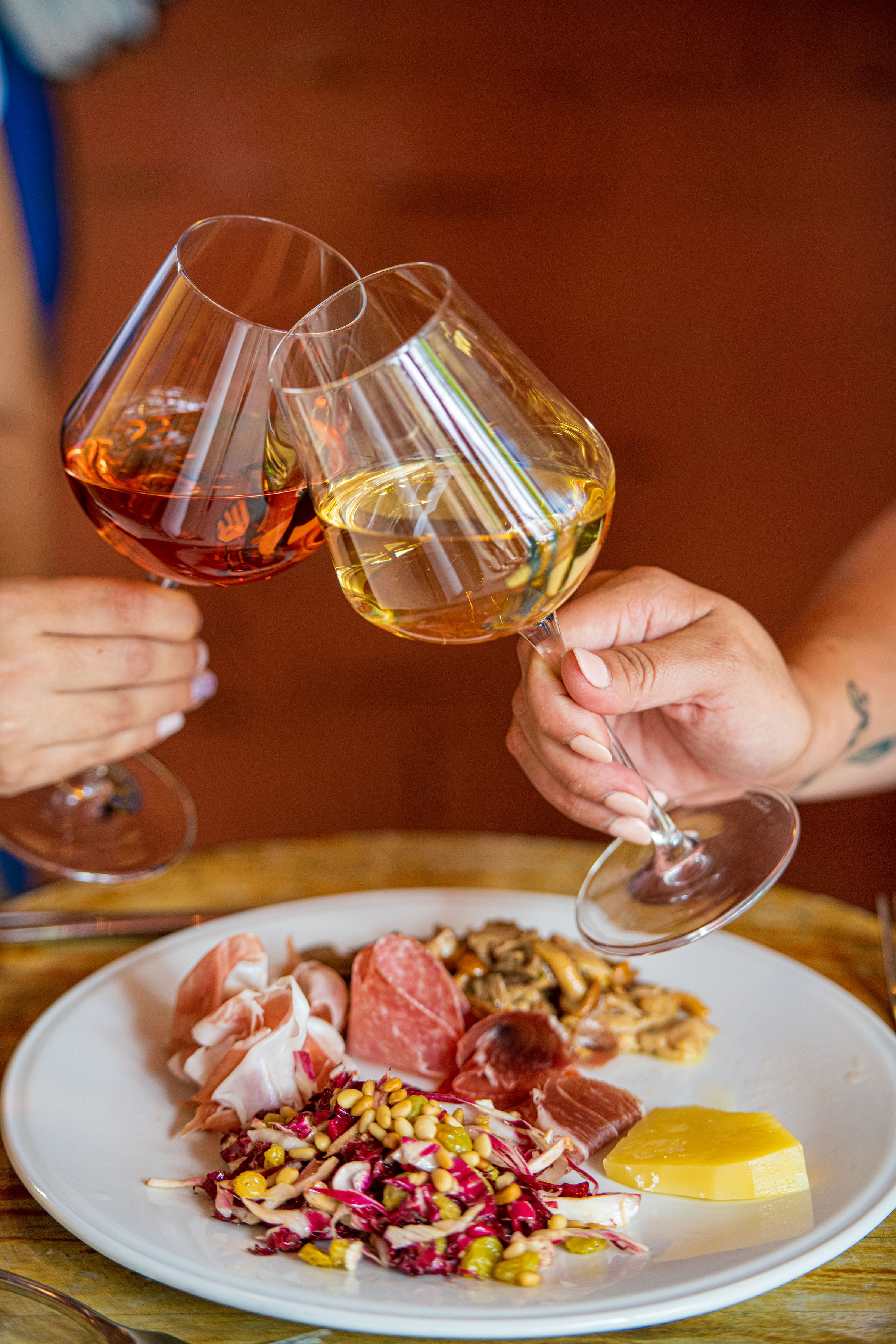 Clinking glasses of rose and white wine above a plate of charcuterie from Storico Vino in Buckhead Atlanta