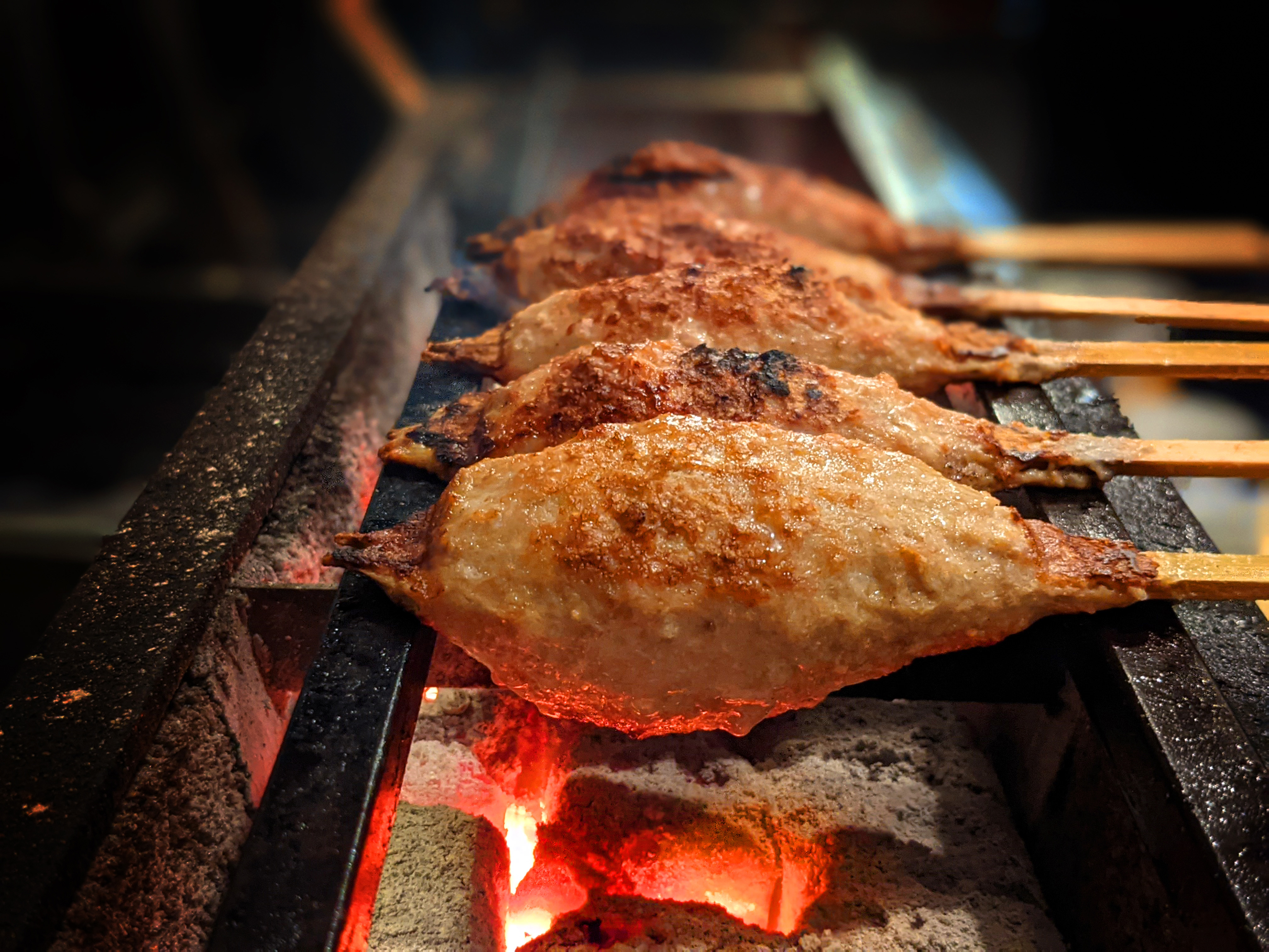 Several meat skewers are lined up over a charcoal grill at Aki Kushiyaki.
