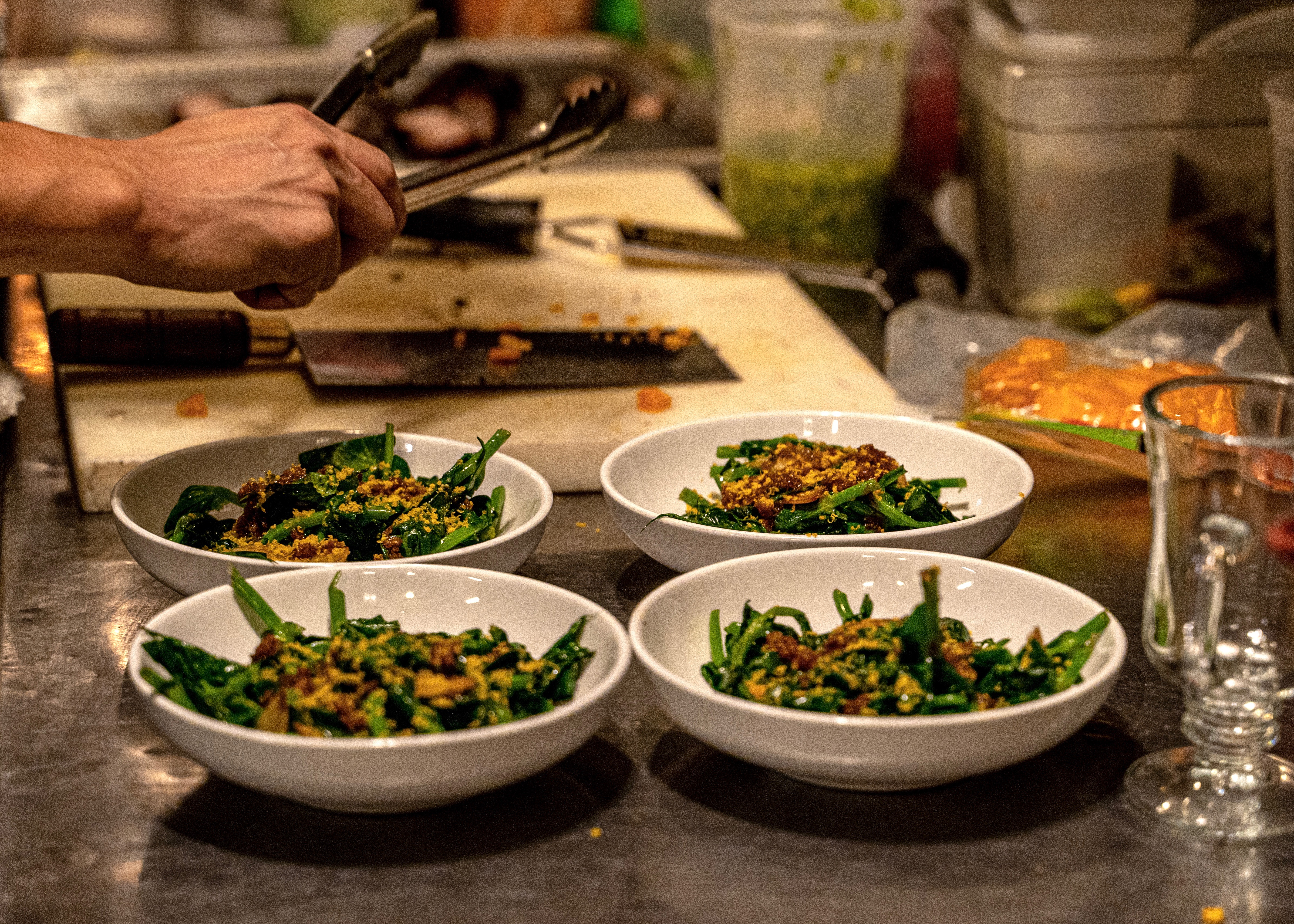 Four white bowls with green vegetables laid out on a kitchen table with hands in the background working over a cutting board