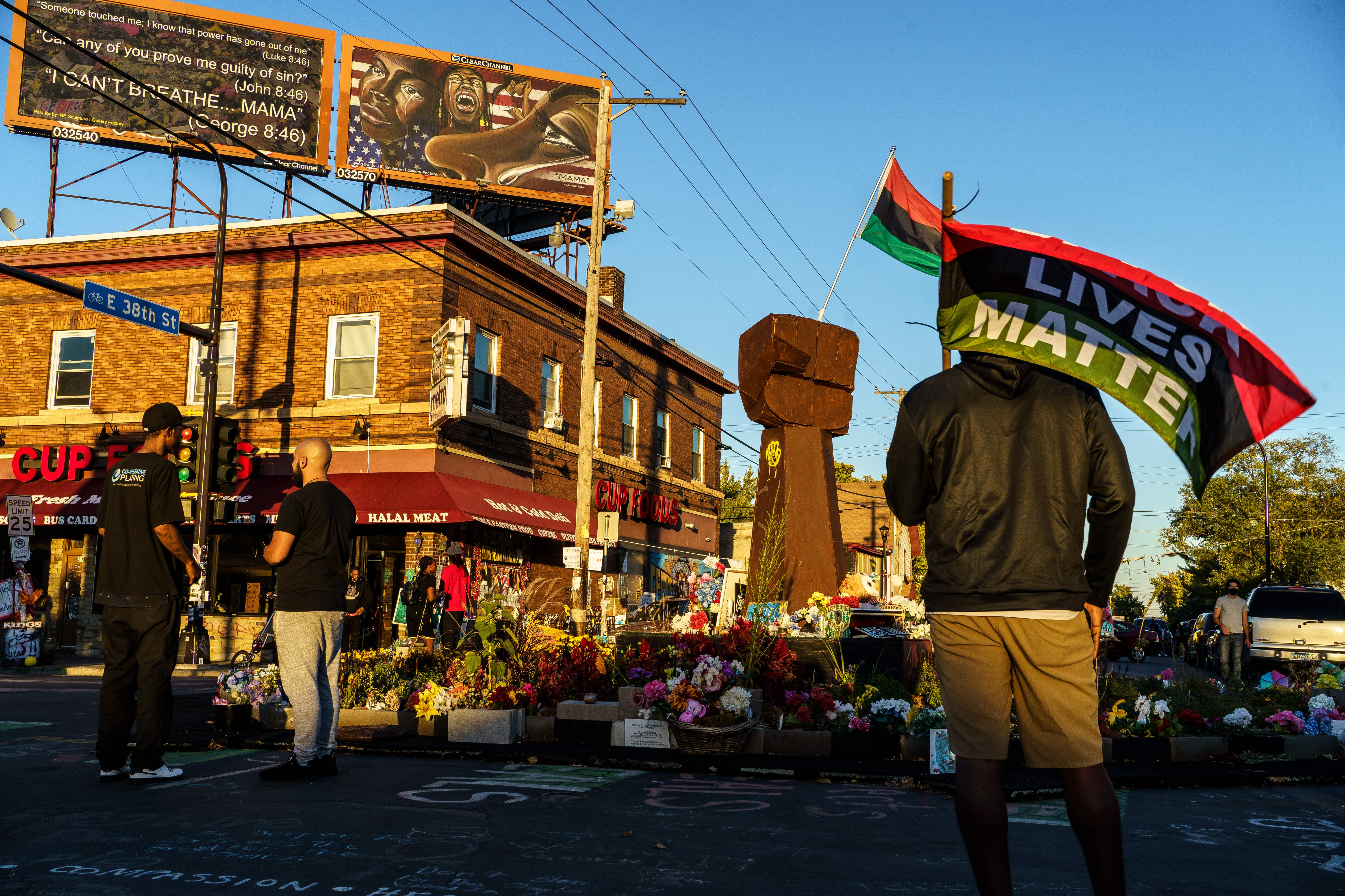 A sculpture of a raised fist rises amid a mass of flowers outside Cup Foods. Two Black men stand in front of the memorial; in the foreground of the photo a Black man in a black hoodie holds a large pan-African flag, with the words Black Lives Matter written on it.